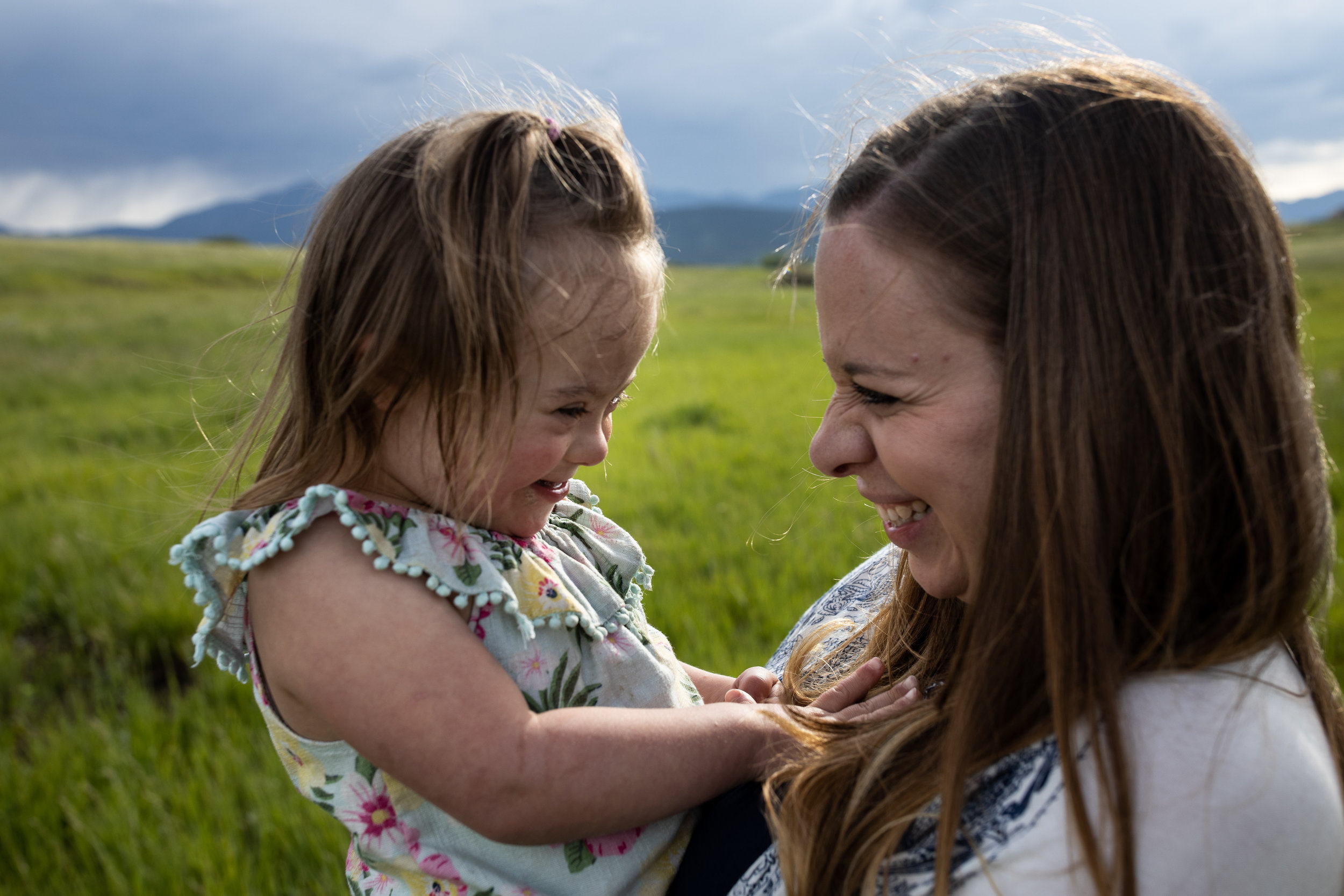 Mom and daughter laughing with mountains in the background
