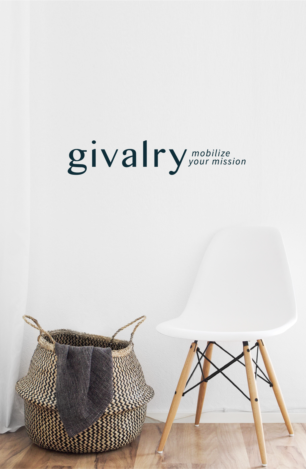 Givalry full logo with motto situated on top of an image of a brown wicker laundry basket with a dark purple blanket sitting on the edge, next to a white backed chair with light wooden legs.