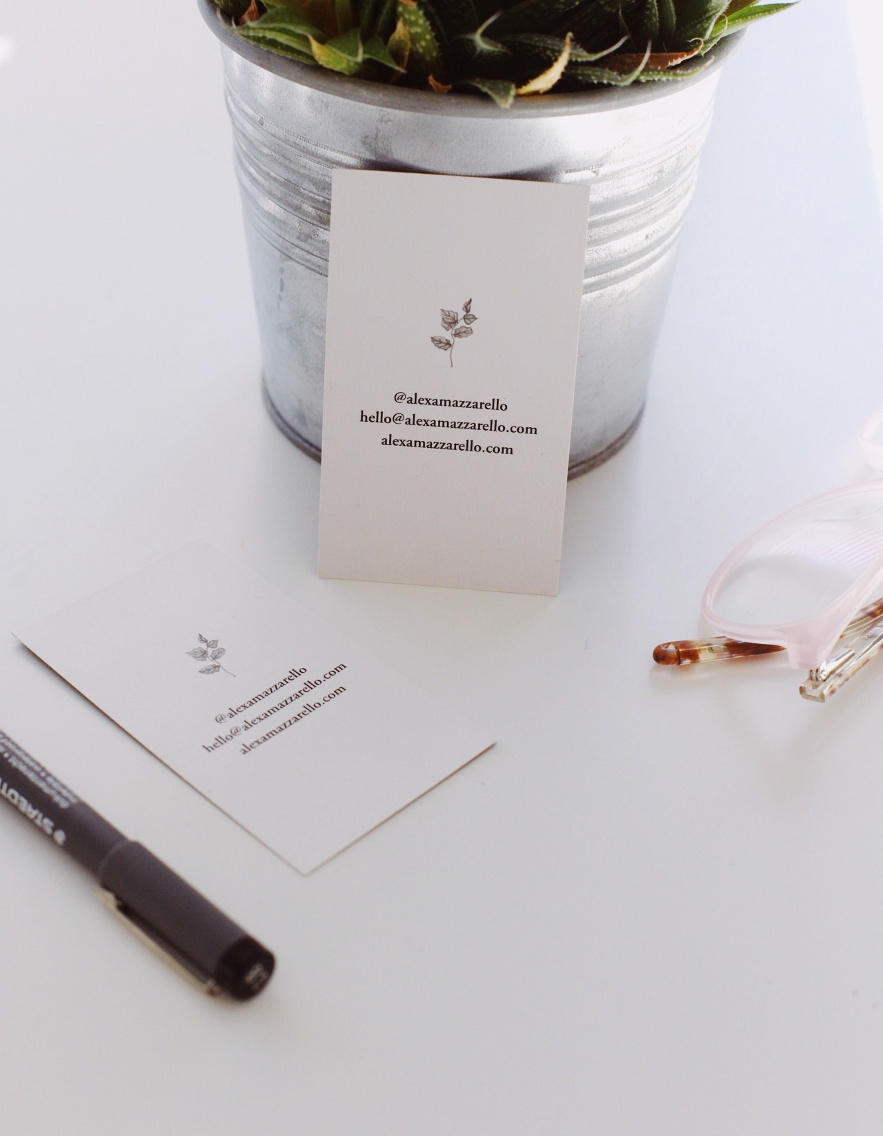 Photo of Alexa Mazzarello's business cards featuring her leaf illustration. Business cards are sat next to pink glasses, a black pen, and a plant in a metal container.