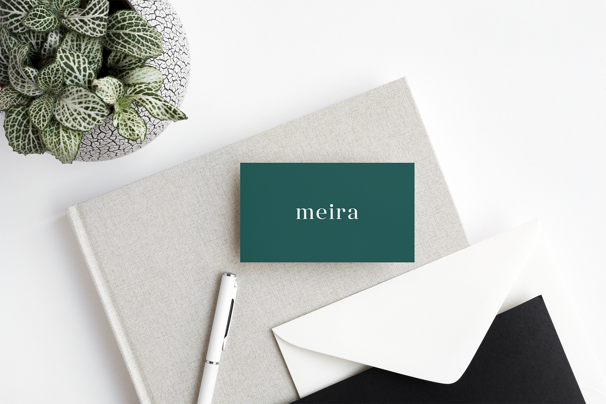 Meira Consulting green business card with m icon on top of a grey notebook with a white pen.