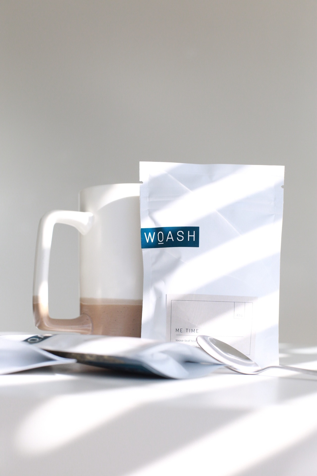 Woash Wellness packaging shown with a spoon and a mug