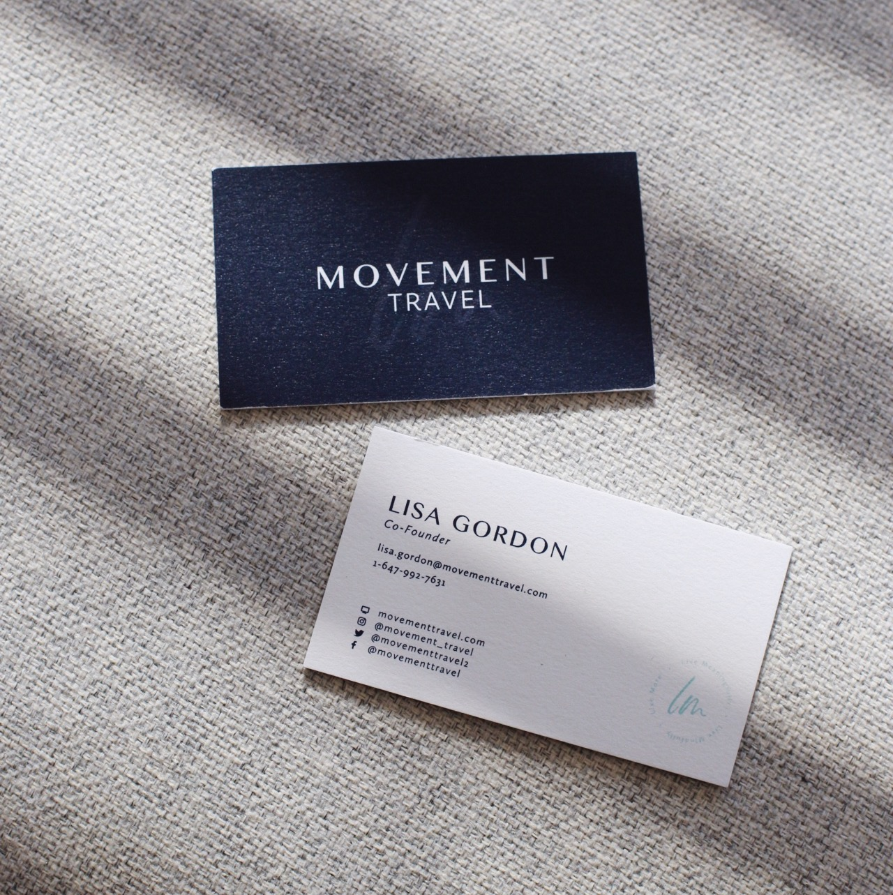 LM Movement Travel blue business cards on grey fabric background