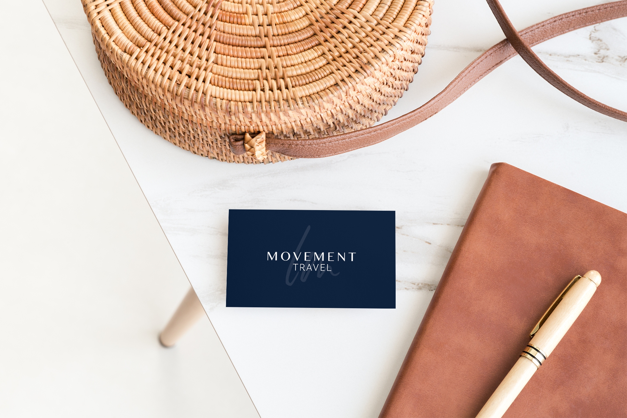 Blue LM Movement Travel business card mockup on a marble table with a wicker handbag