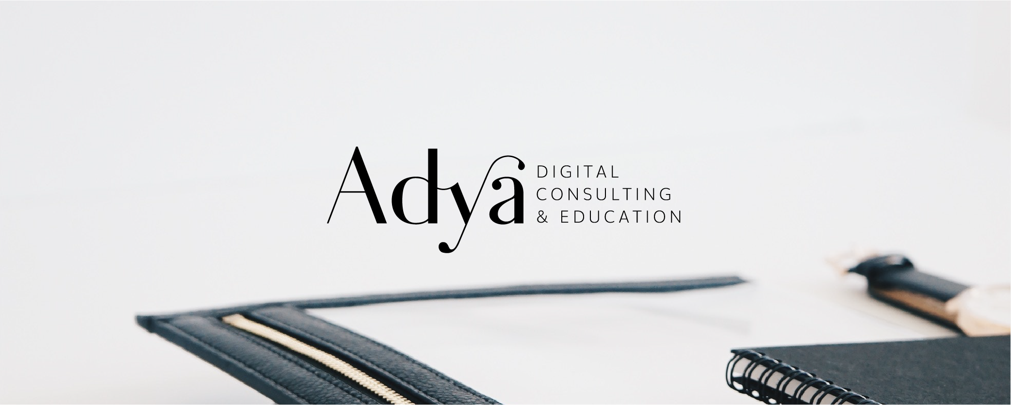 Adya Digital Consulting and Education logo on a photo of notebooks