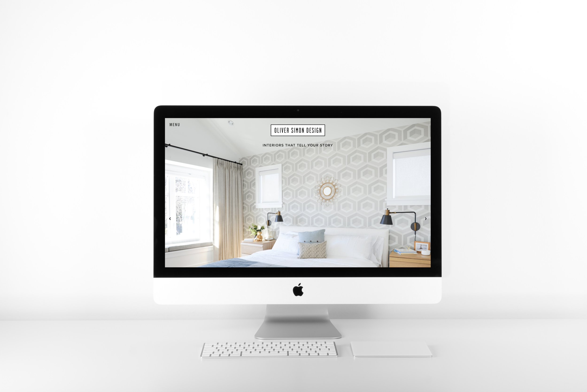 Oliver Simon Design's website homepage is shown on an iMac with plants and other office paraphernalia around it.