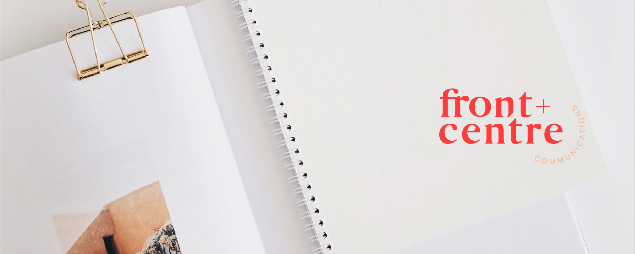 Front + Centre logo in red on a photo of a spiral bound notebook that is at an angle