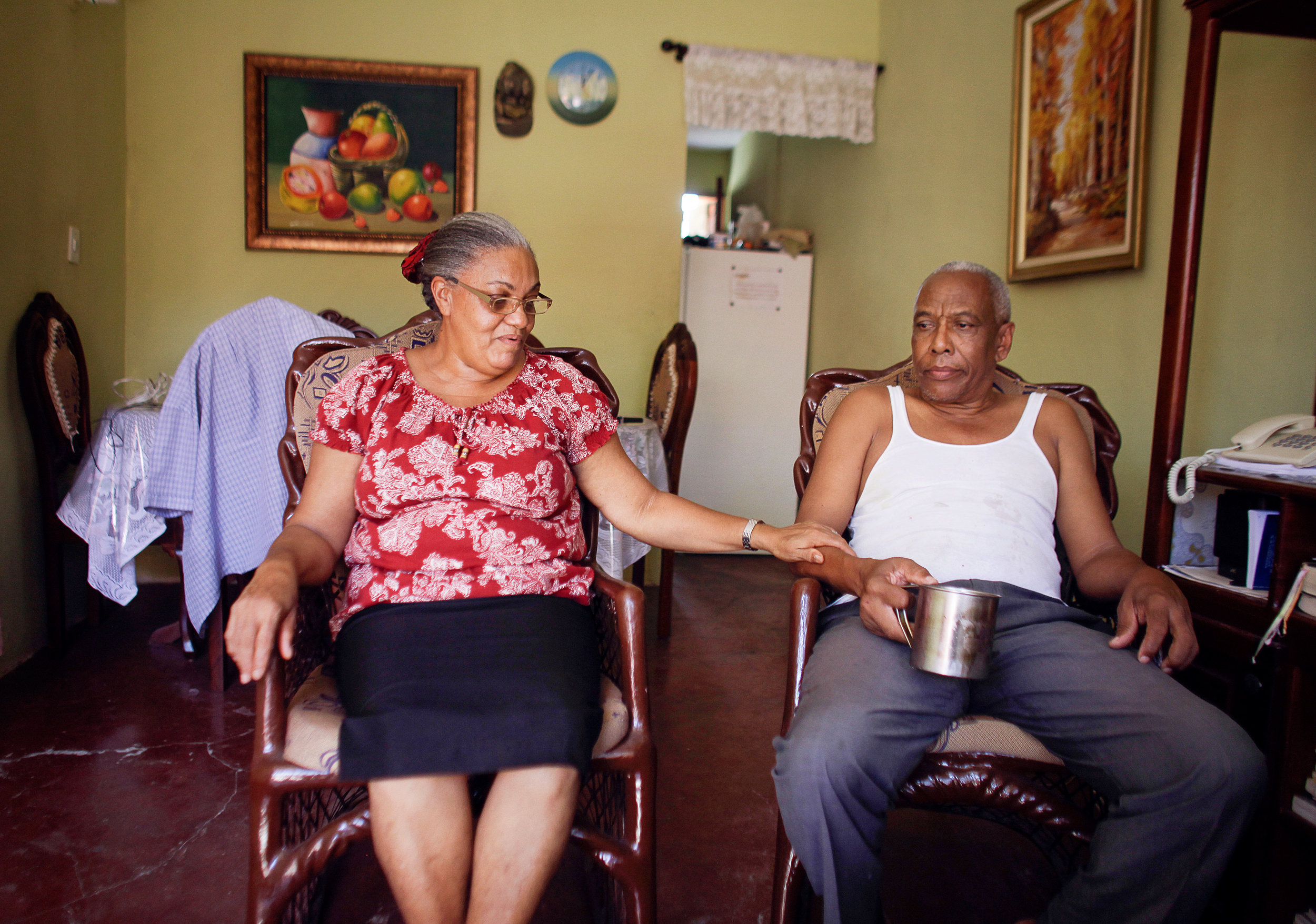 Domitilia takes the hand of her partner, Salvador, in their home in Santo Domingo, Dominican Republic. At 57 years old, Domitila has diabetes, but she still successfully recovered from tuberculosis after two years of treatment.