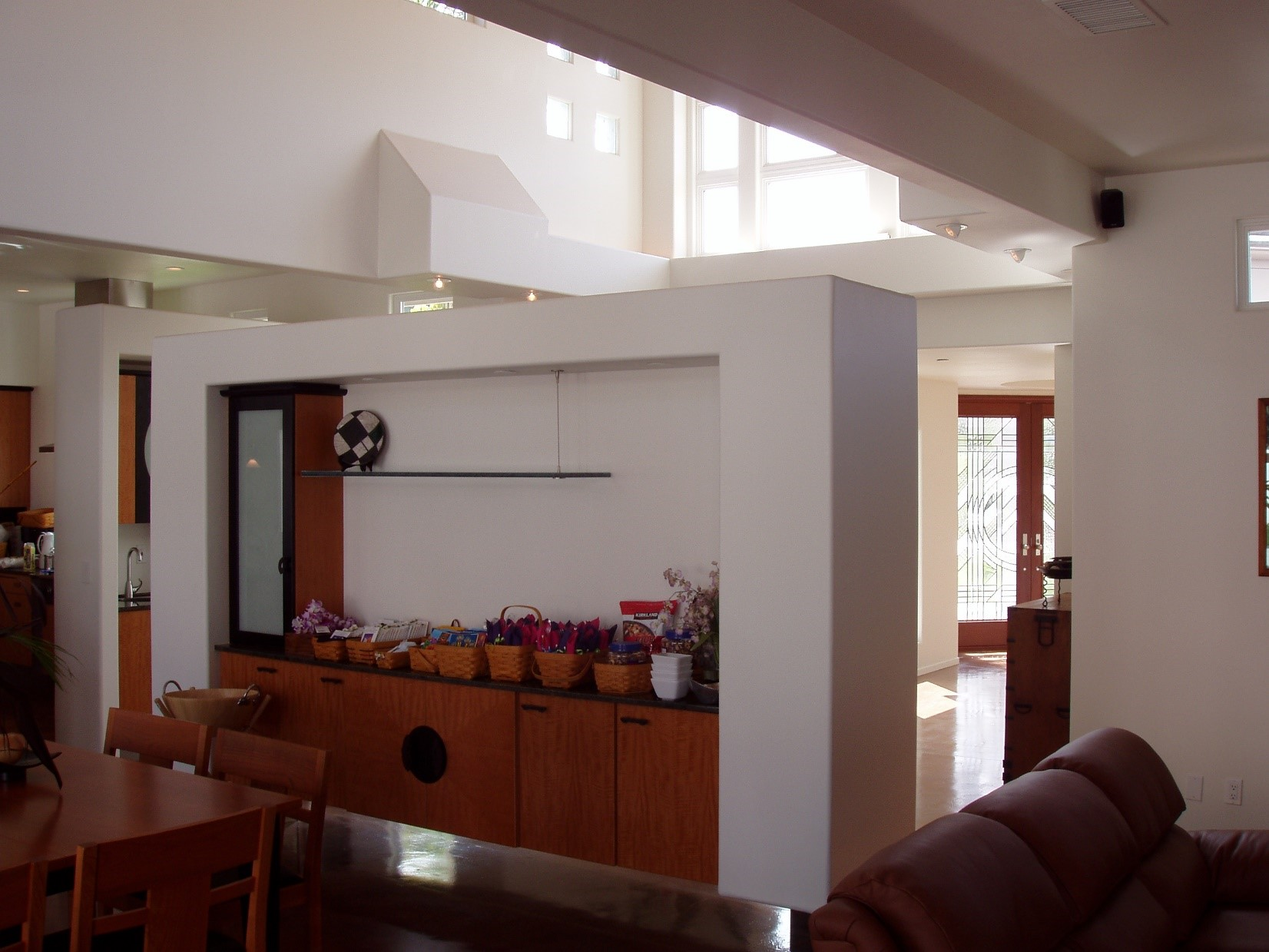 The Great Room side of the Floating Wall containing storage and a small buffet platform serving the dining room table.The Foyer and entry doors can be seen to the right, beyond.