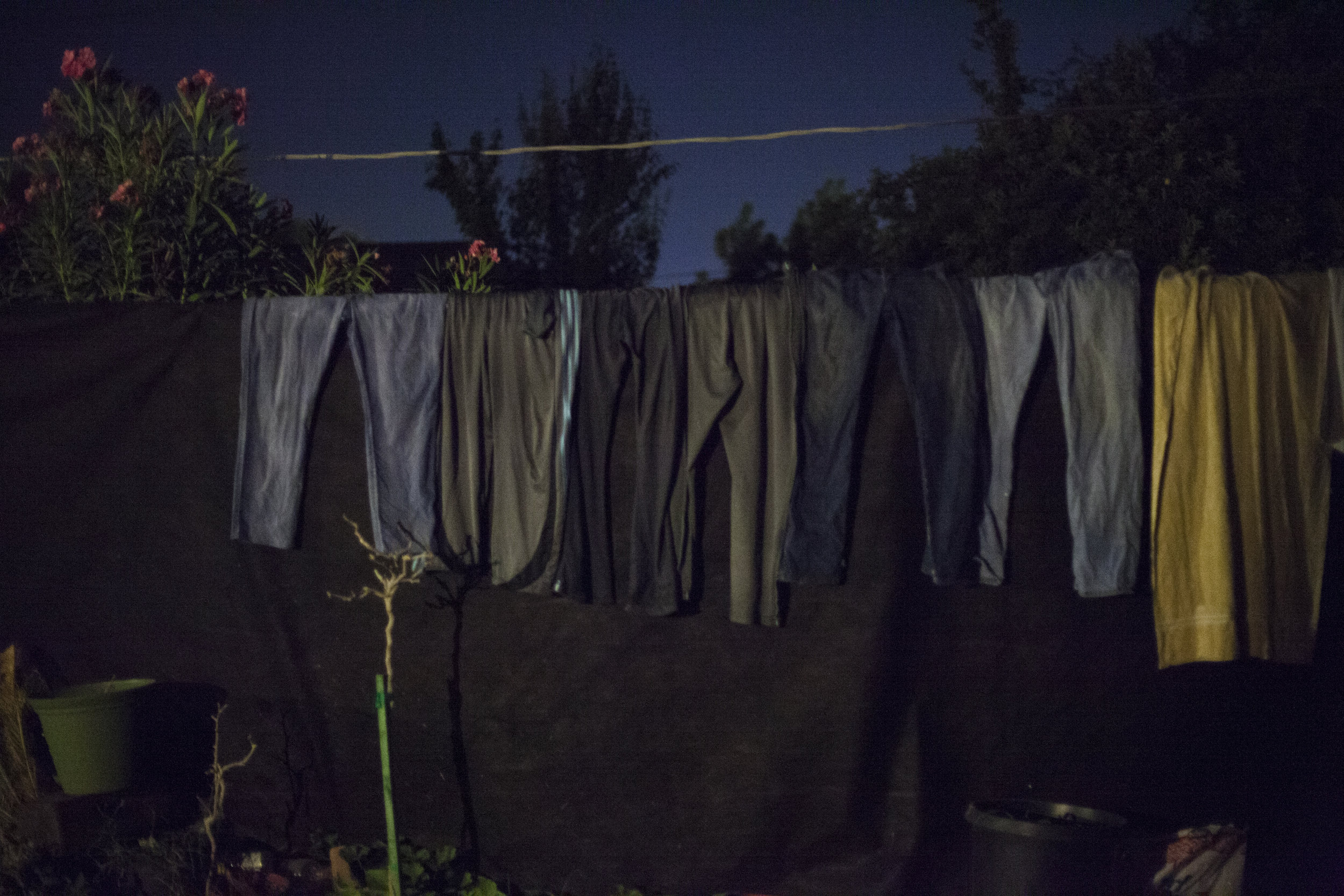 A clothing line full of wet clothes sits on the fence in Blanca's backyard in Bakersfield, CA. Photographed on August 24, 2013.