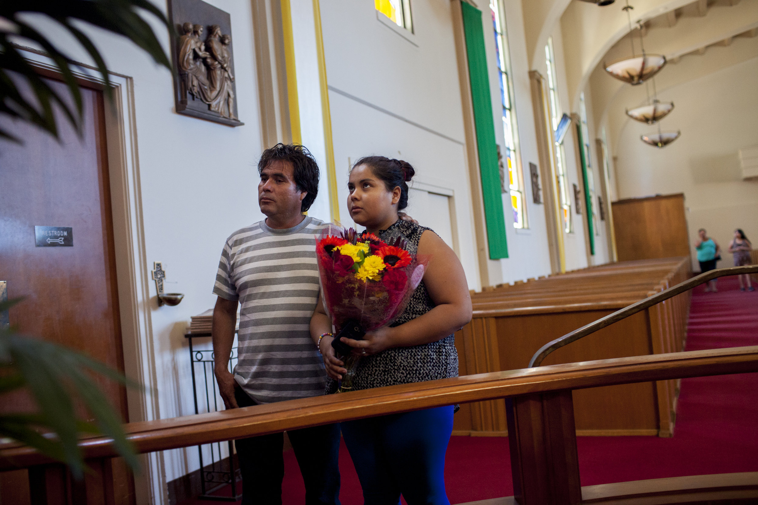 Blanca and her father Eduardo pay tribute to the Virgin of Guadalupe at the start of her second semester of UC Berkeley in Berkeley, CA at an unspecified church. At the start of each semester she pays tribute by bringing flowers to the Virgin to thank her. Photographed on August 27, 2013.