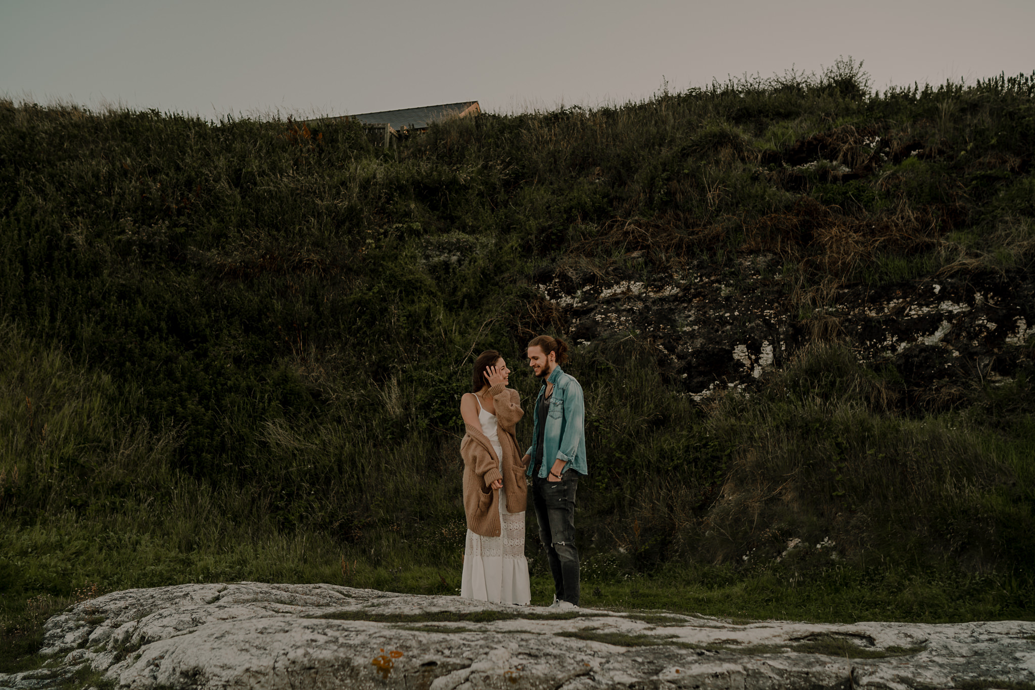 cute hipster couple laughing during an engagement shoot on the causeway coast