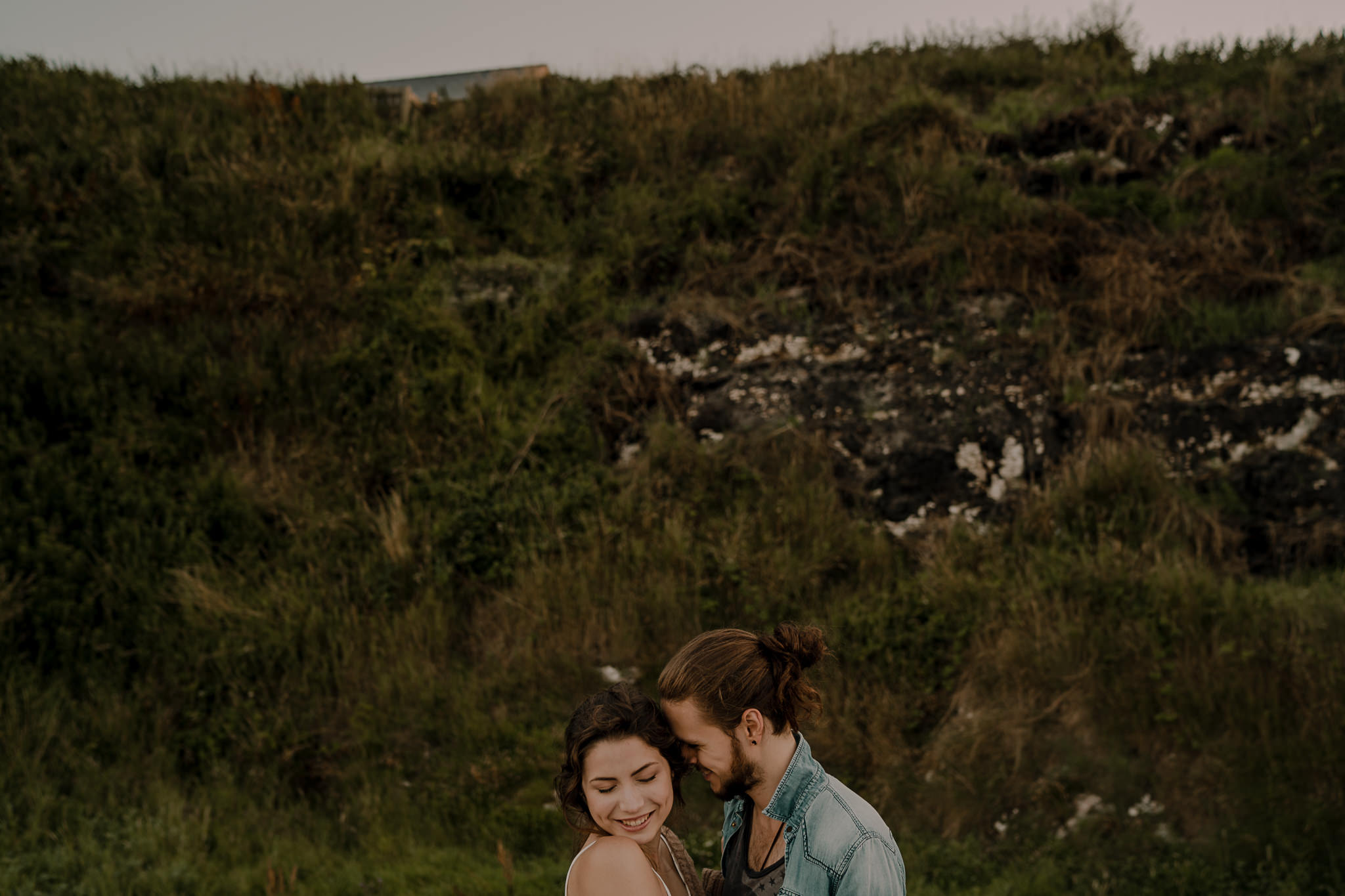 sweet guy whispers in her ear during engagement shoot on the causeway coastal route