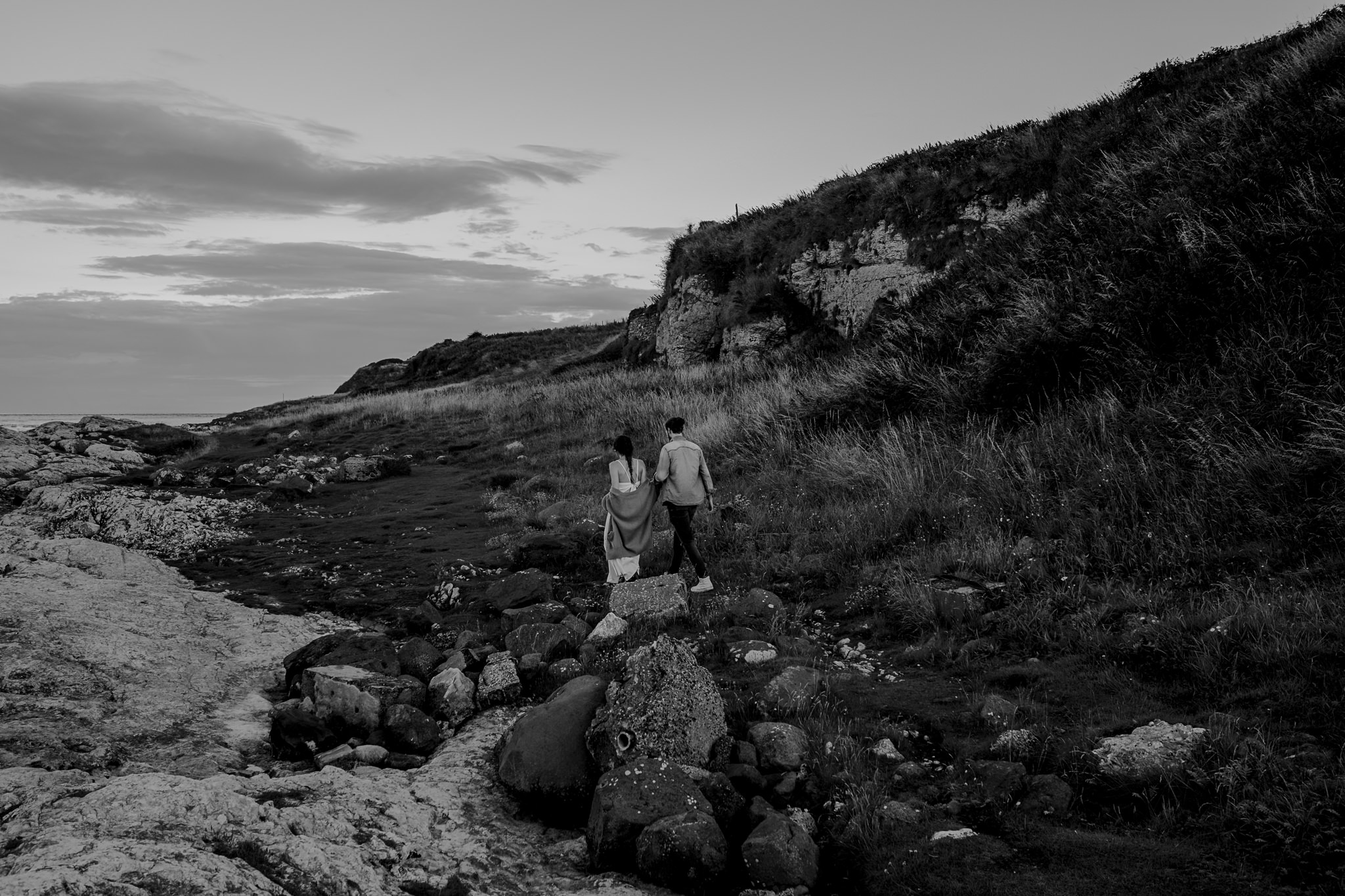 couple walking over rocks on the causeway coastal route engagement photographer