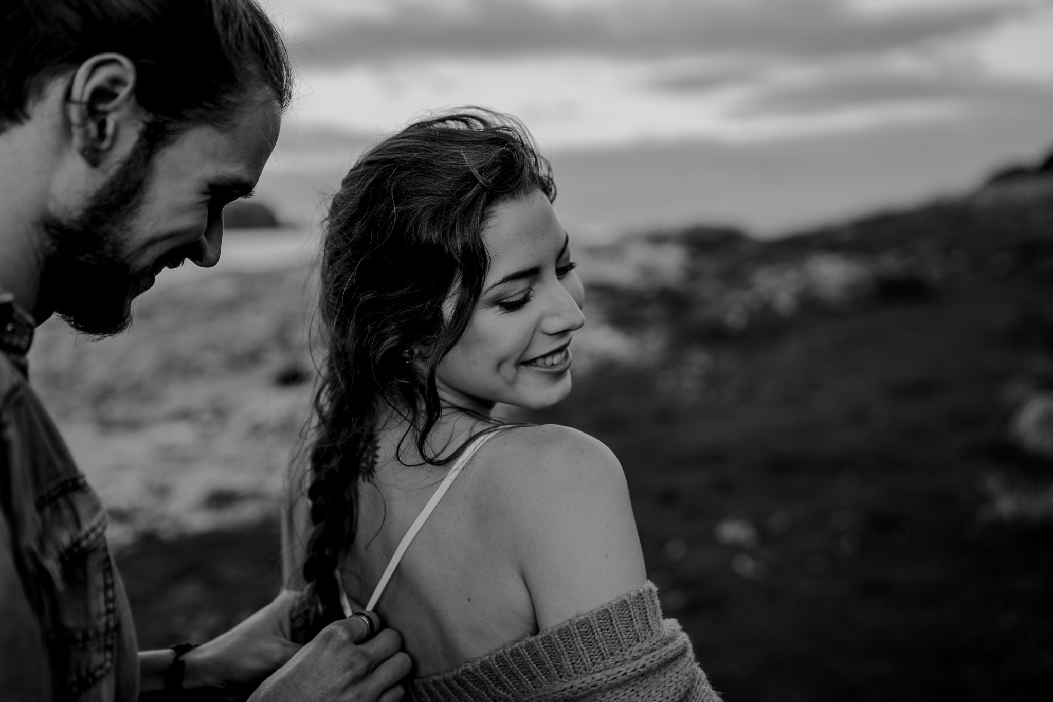 fixing her dress during an engagement session on the causeway coast