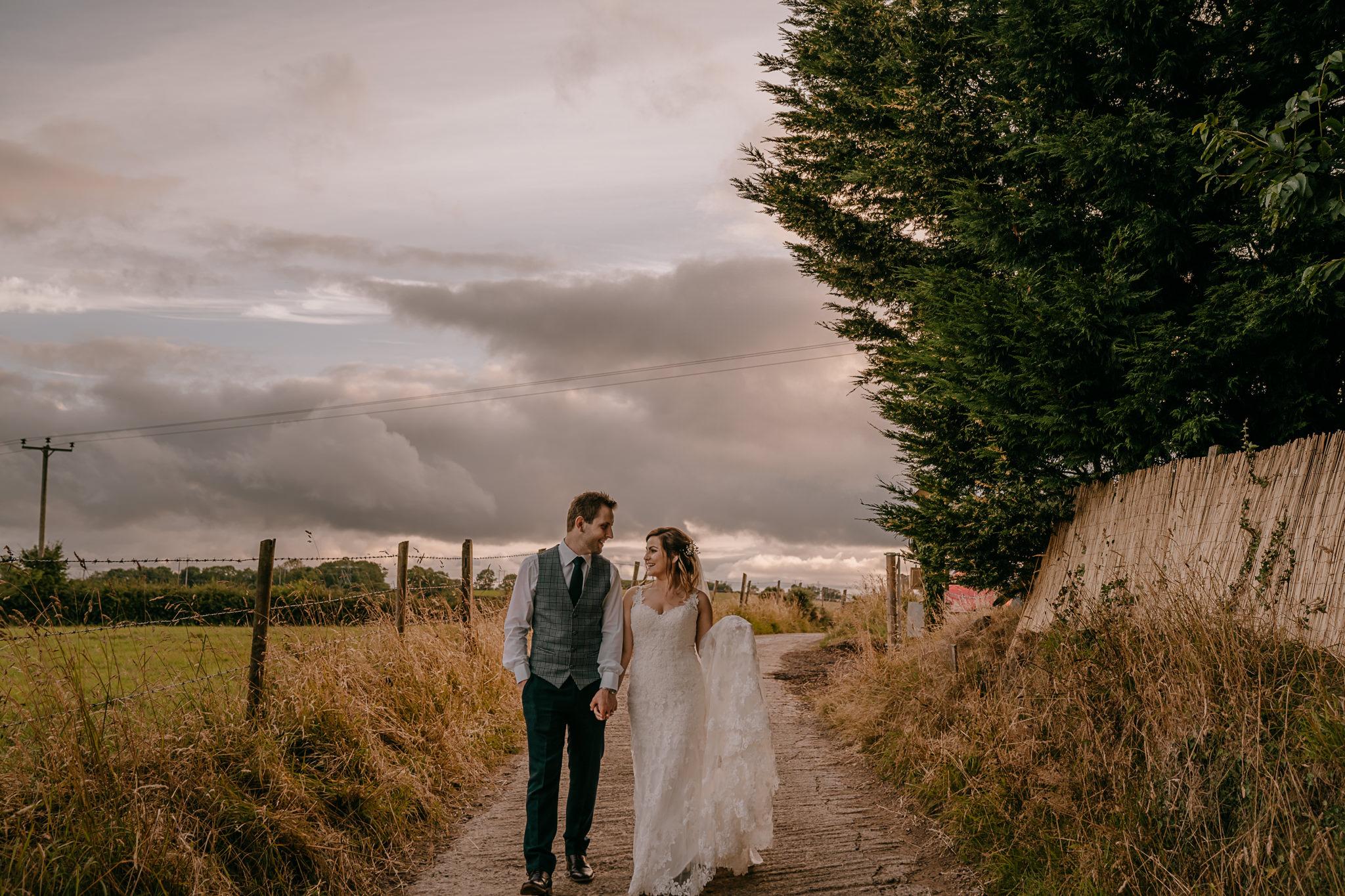 happy couple bride and groom walking on path northern ireland, stella york wedding dress