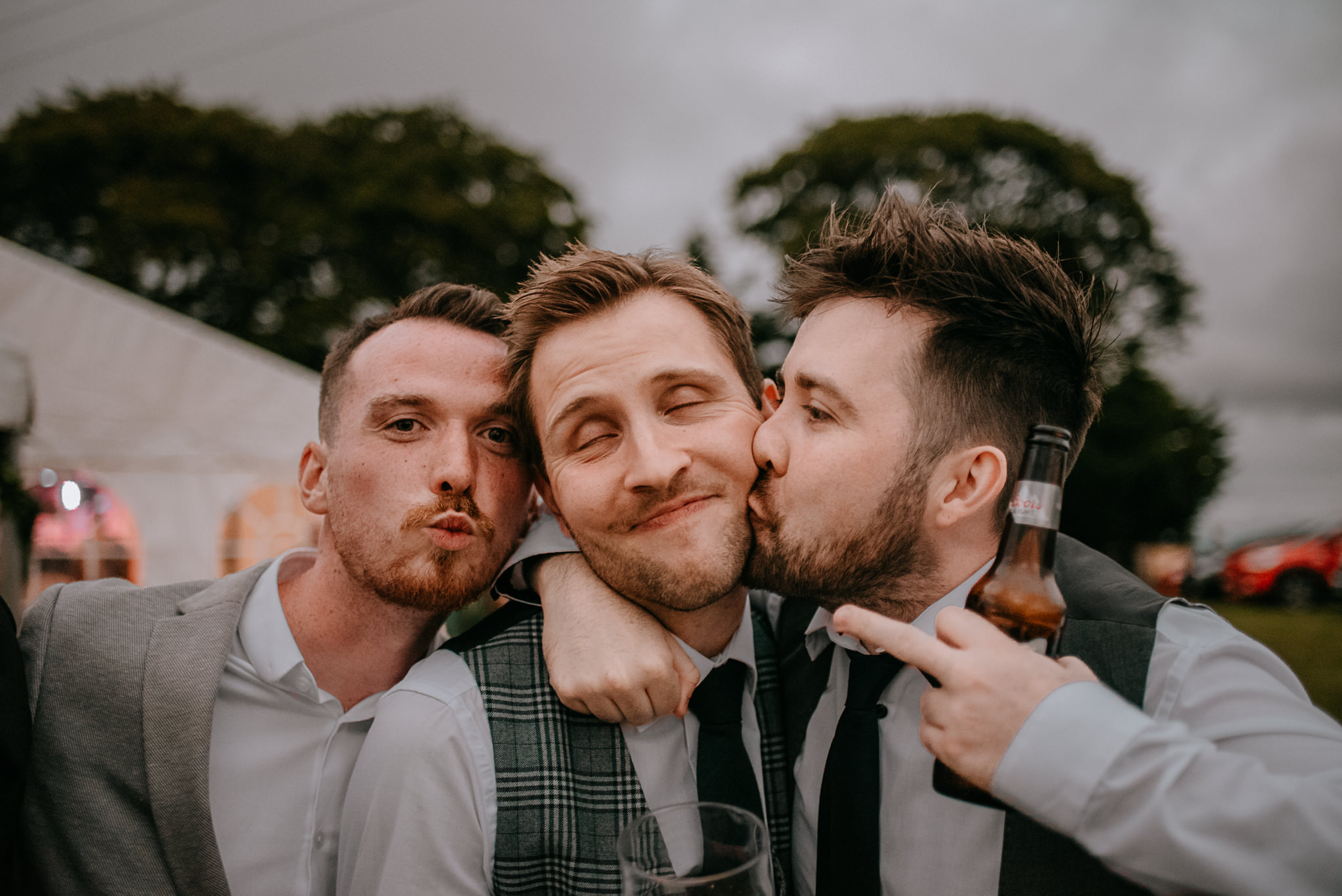 groom and guests silly wedding reception outdoors