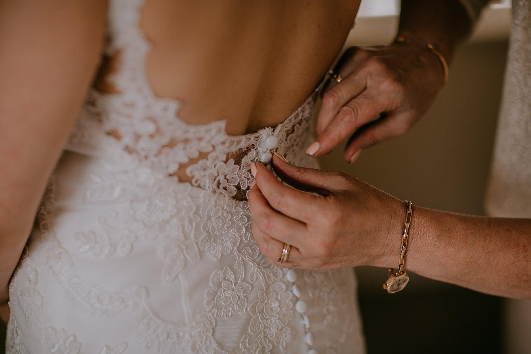 mother of bride buttoning wedding dress details Northern Ireland Wedding Photographers