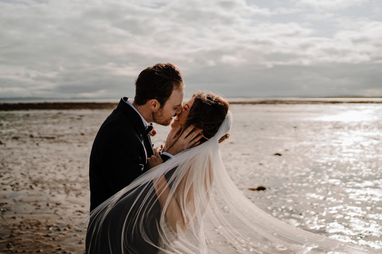 Orangetree House Wedding winswept sunset lough shore veil bride groom kiss