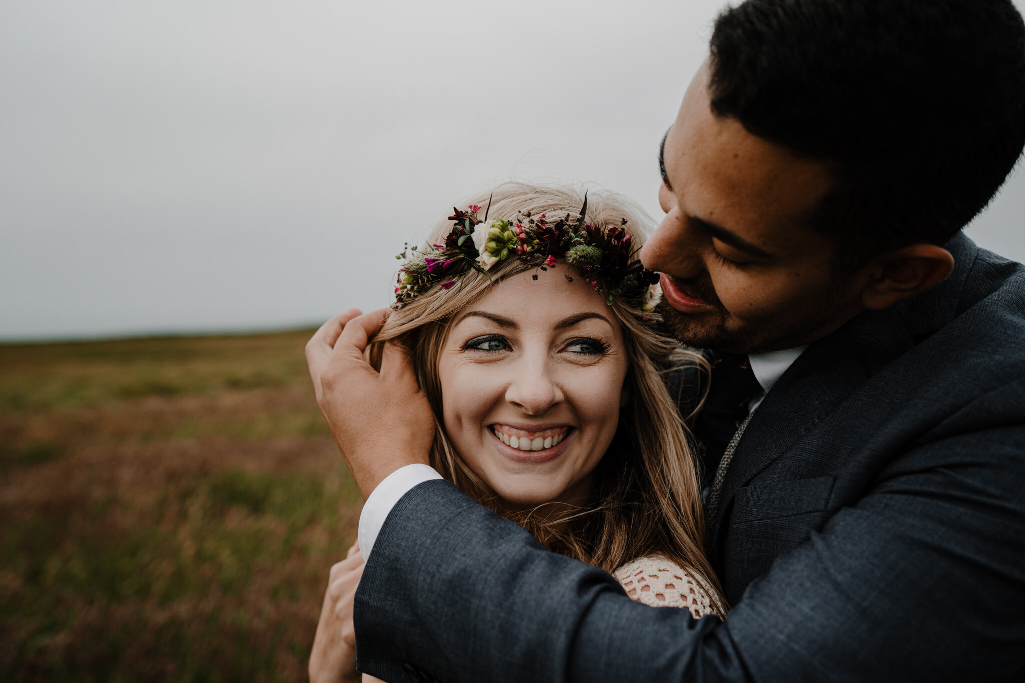 husband strokes hair of wifes face smiling flower crown ireland cliffs of moher anniversary session