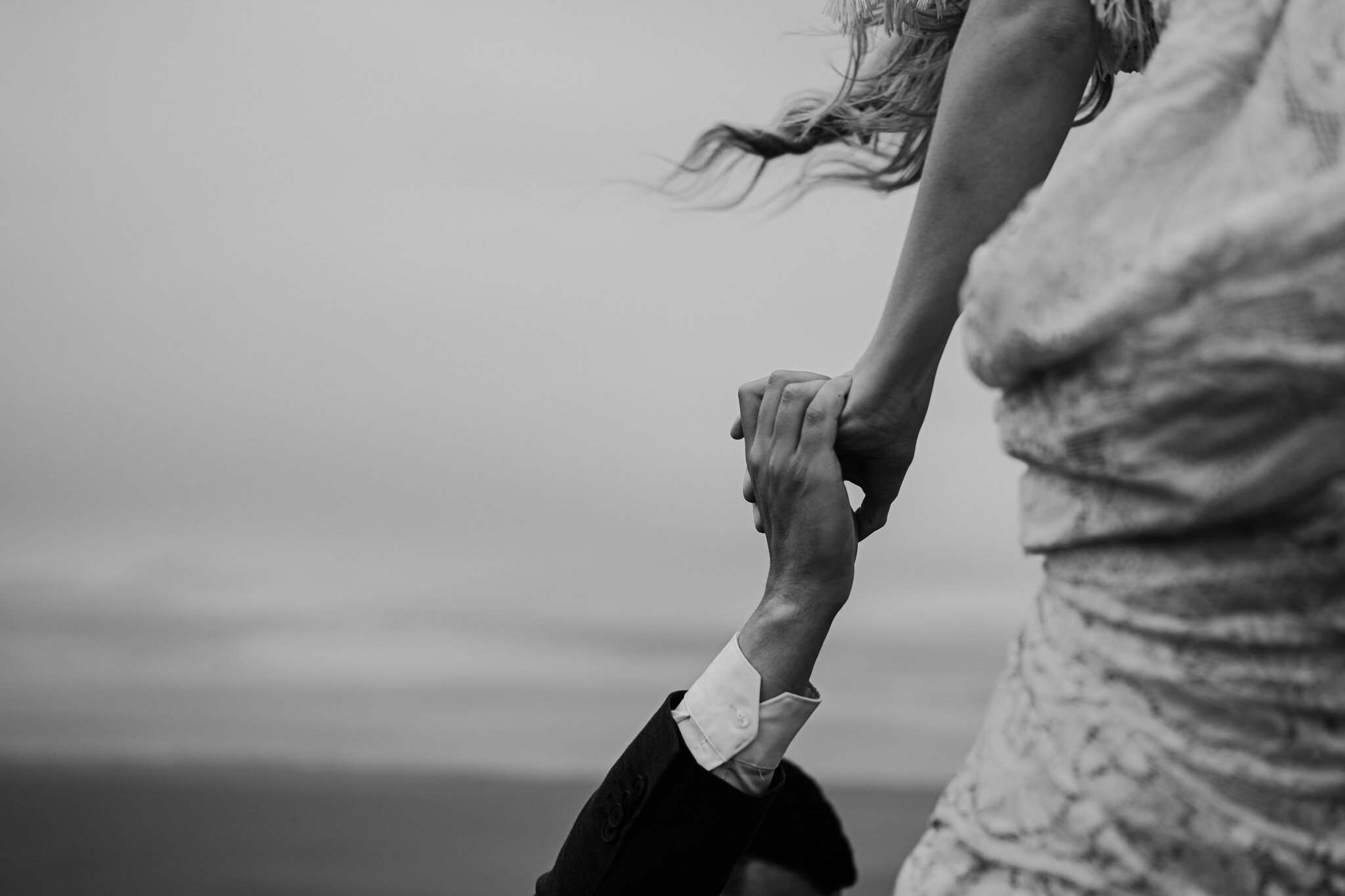 bw closeup husband helps wife over fence at cliffs of moher adventure elopement