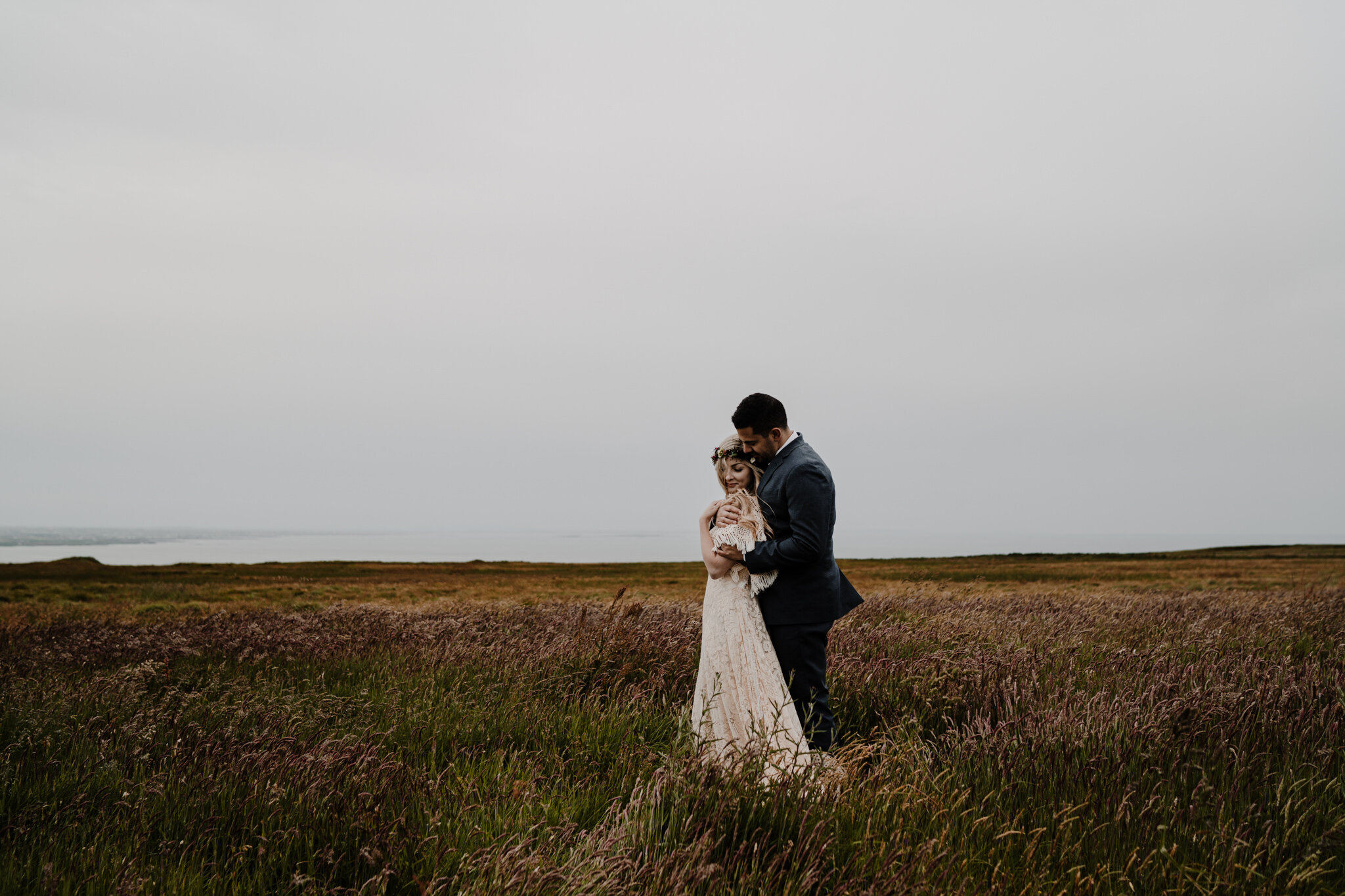 husband and wife stand in irish field hugging at cliffs of moher adventure elopement