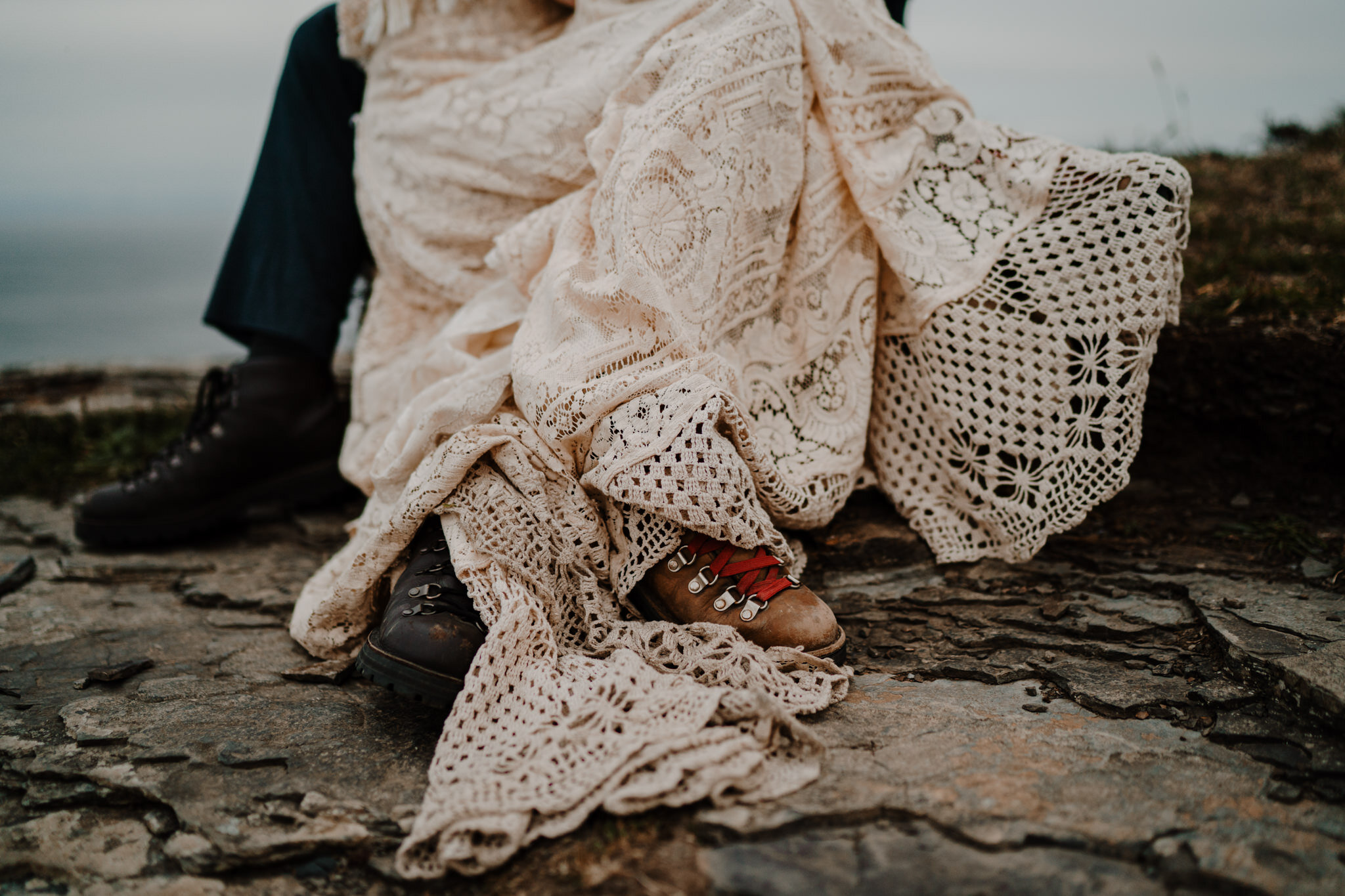 close up danner hiking boots and custom lace reclamation wedding dress Cliffs of Moher ireland