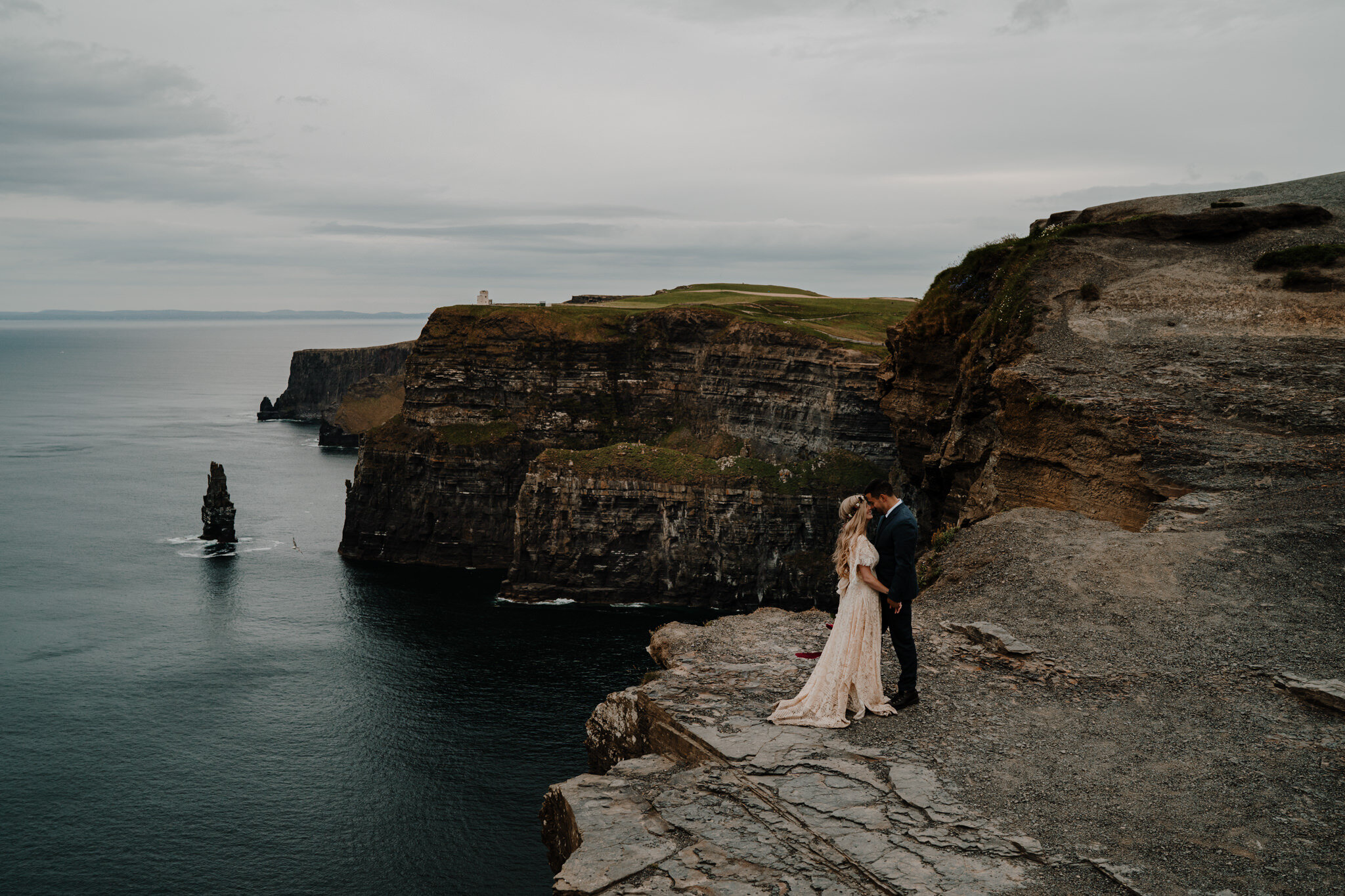 boho couple stand on cliff edge at cliffs of Moher session