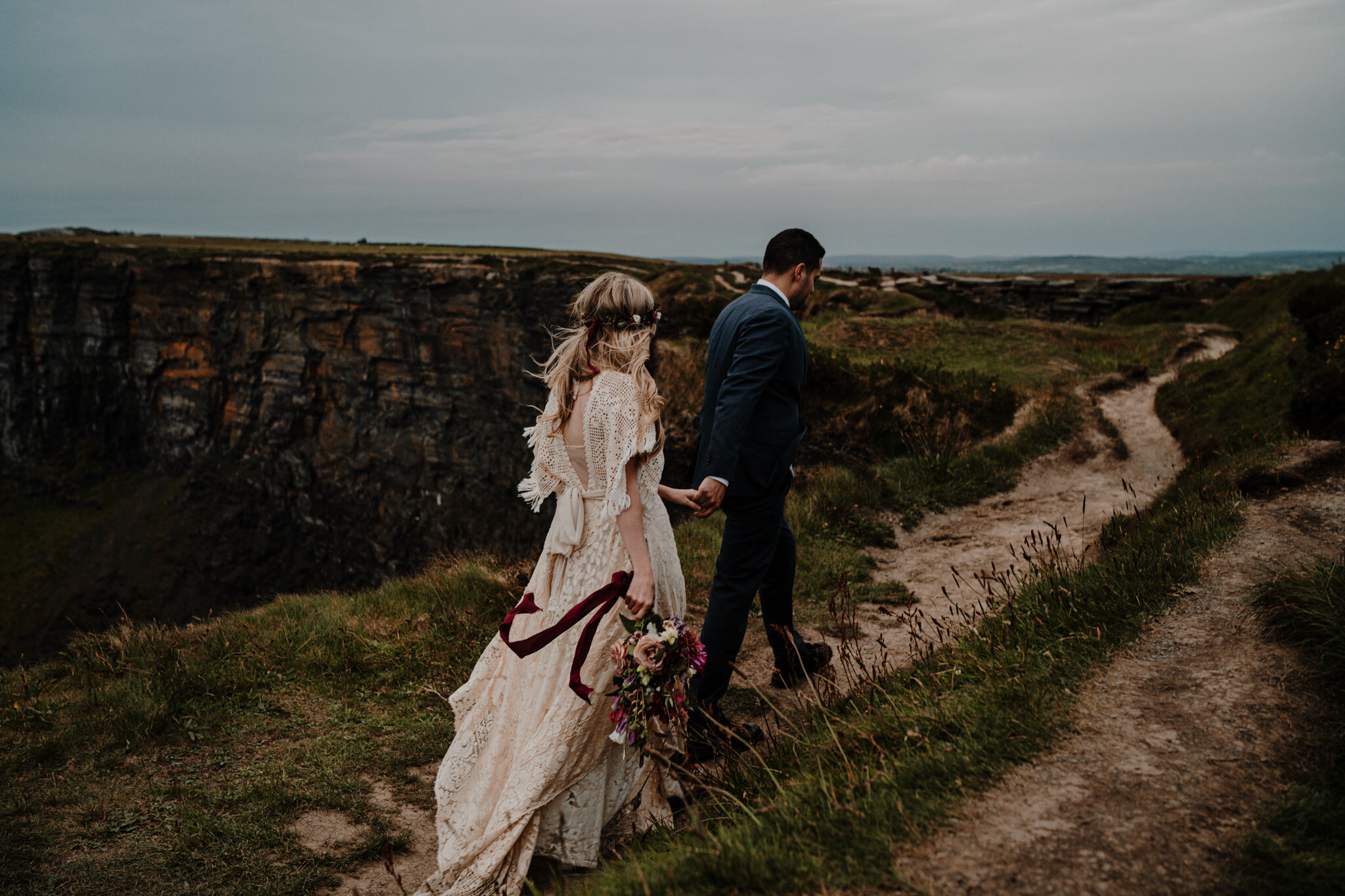 couple walk along cliff edge adventure elopement cliffs of moher ireland