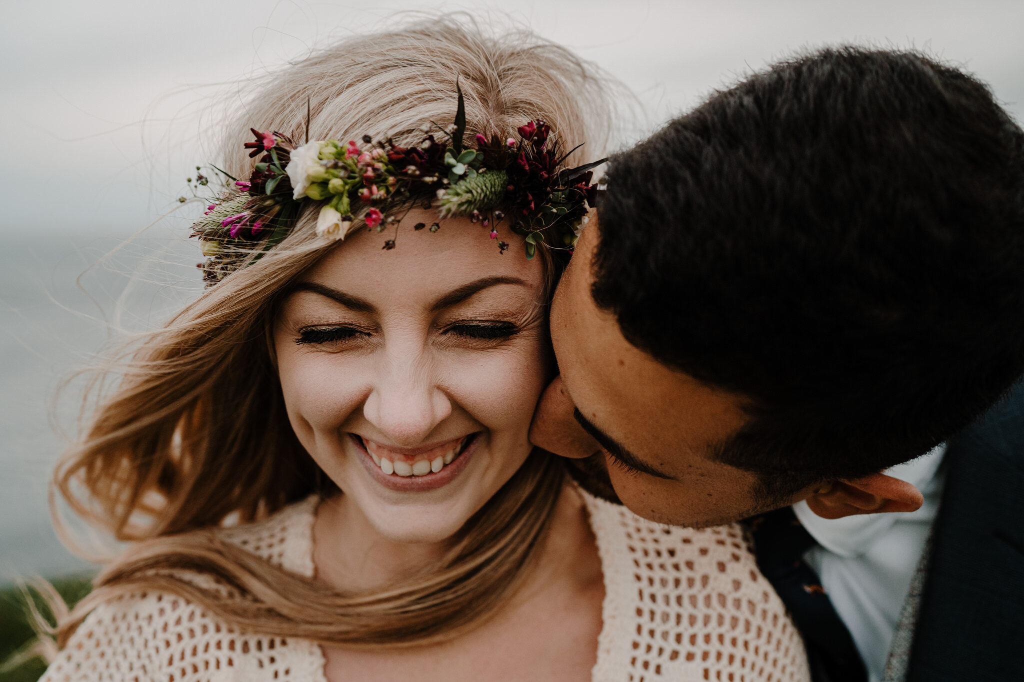 cute boho couple laughing close up kiss on cheek Cliffs of Moher ireland