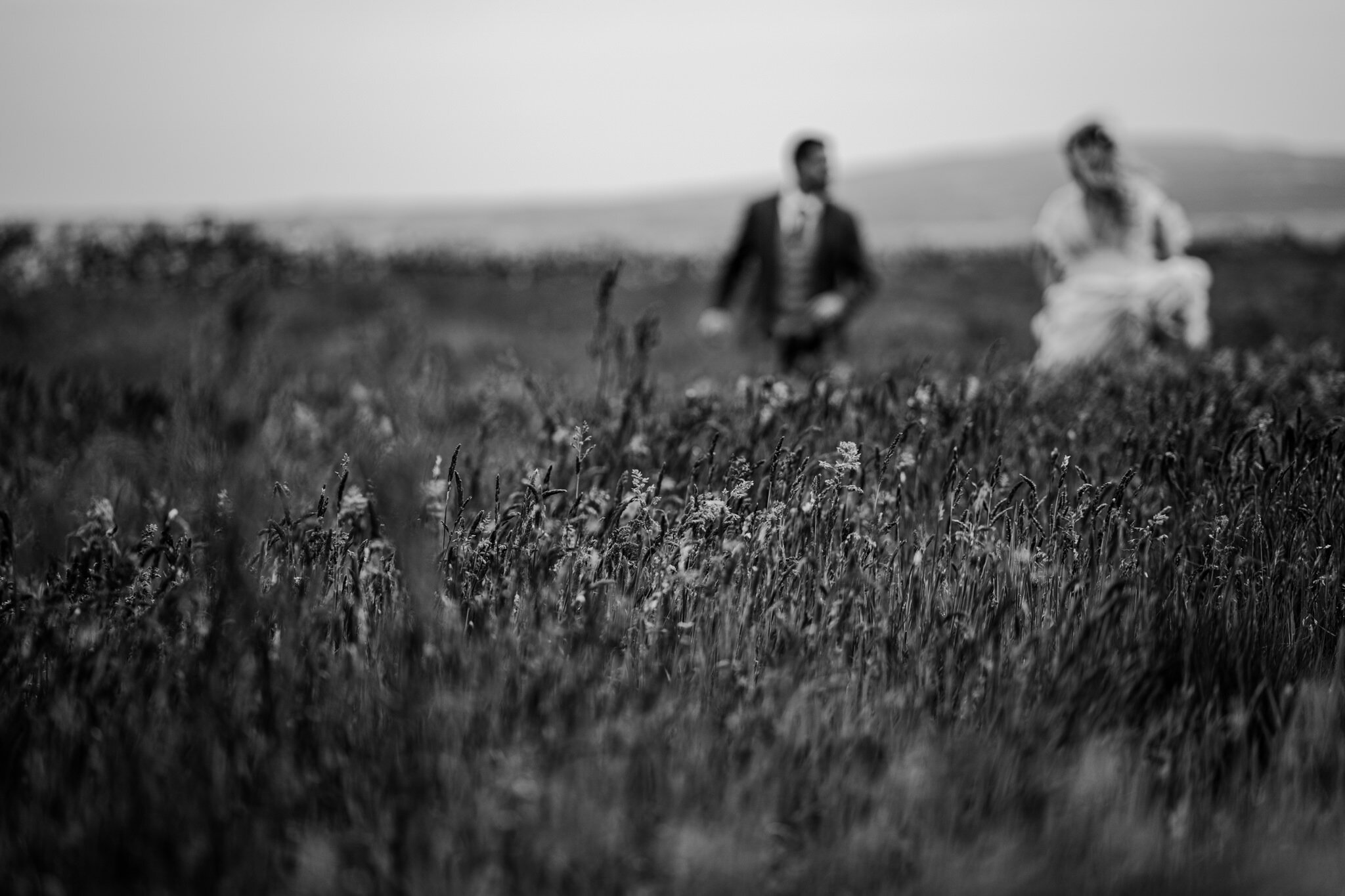 bw couple running through field cliffs of Moher Ireland