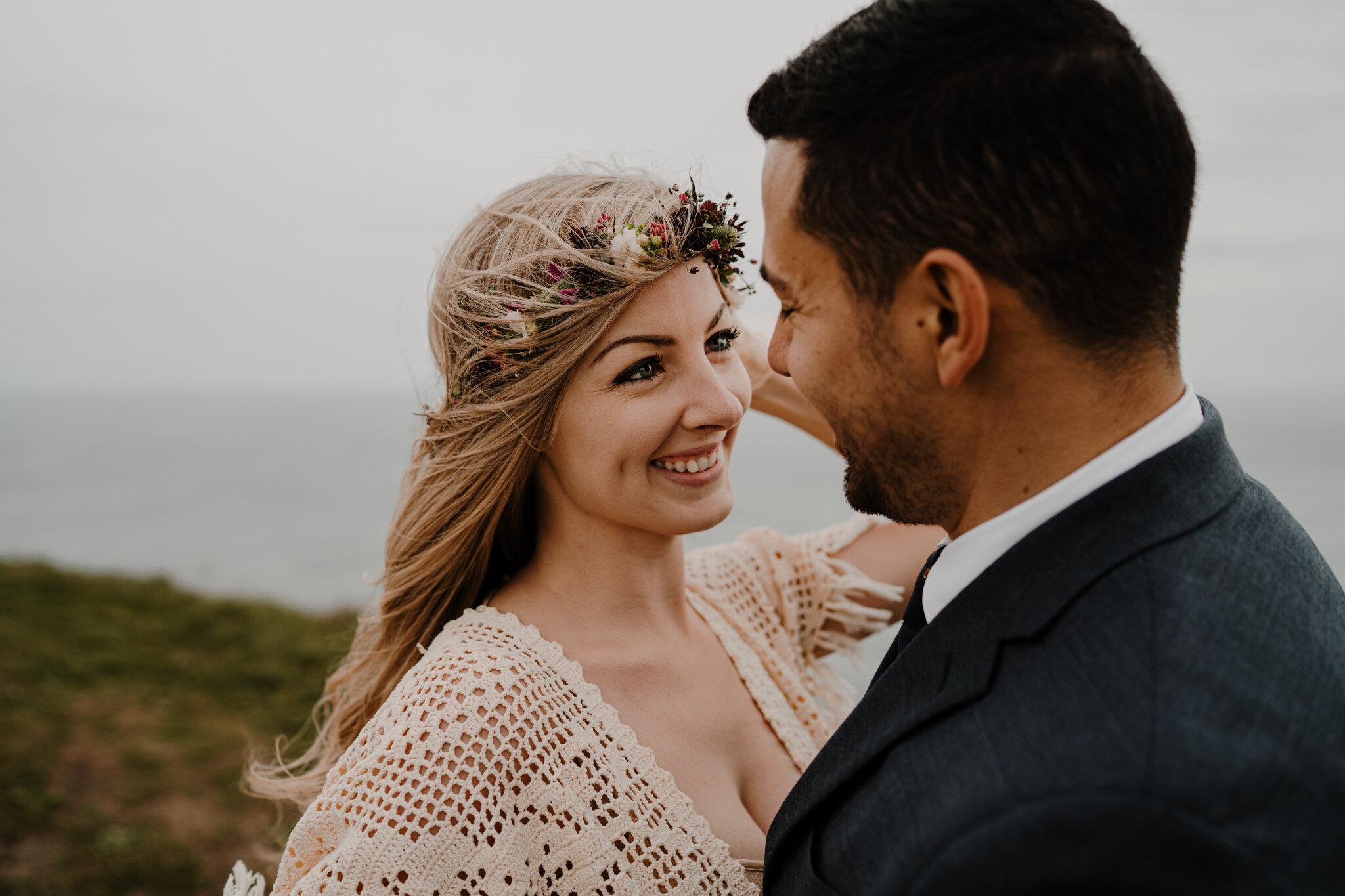 wife smiles at husband floral crown windswept hair at cliffs of moher