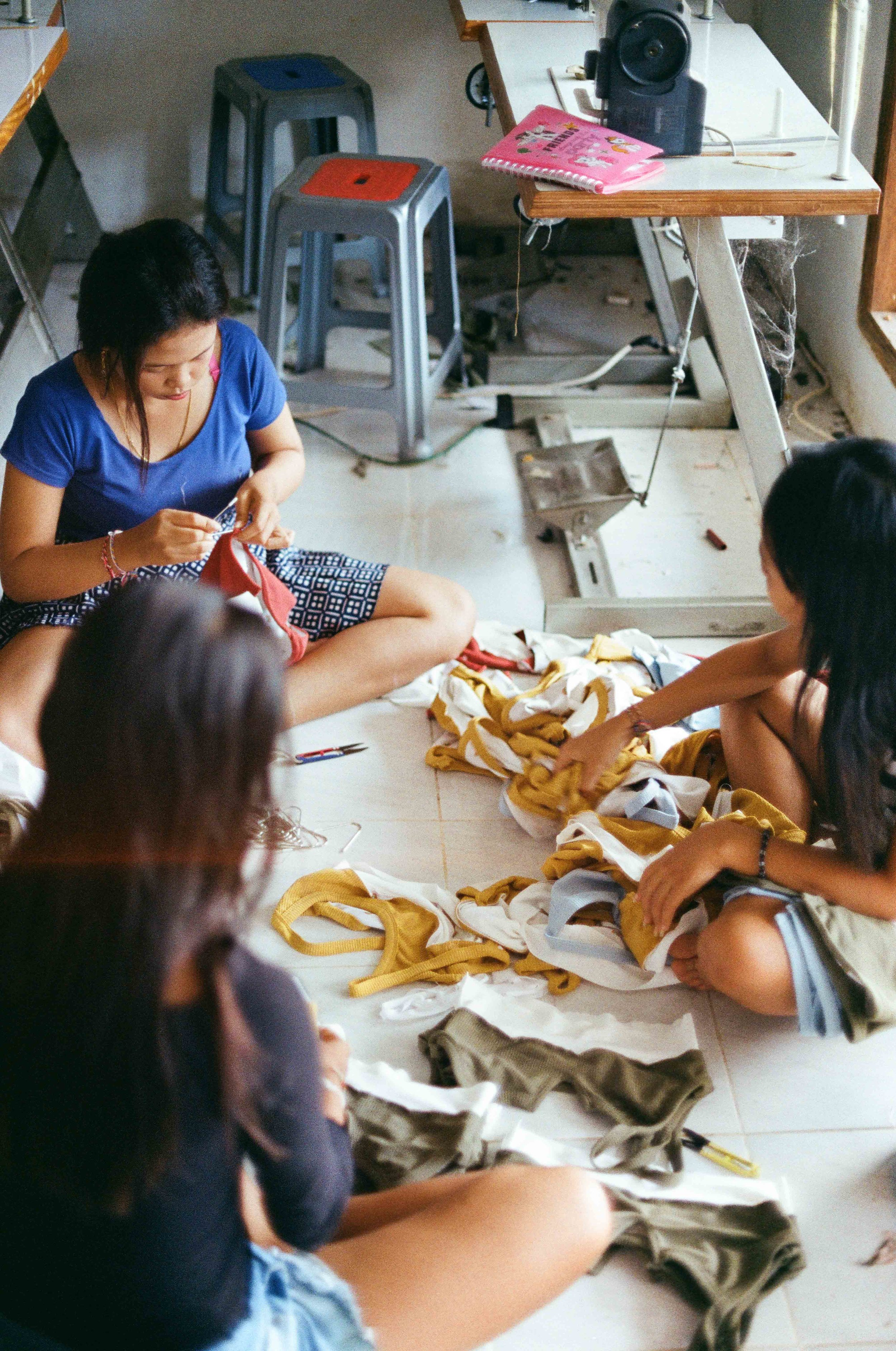 On the hotter days in Bali the tiled floor is the coolest place to sit. Our tailors + seamstresses testing the safety stitching for durability.