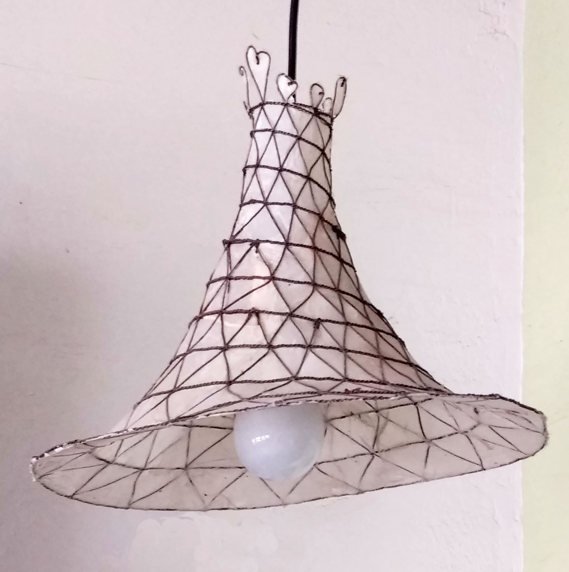 This flared pendant light has a creamy-colored natural rice paper under a woven steel wire net.