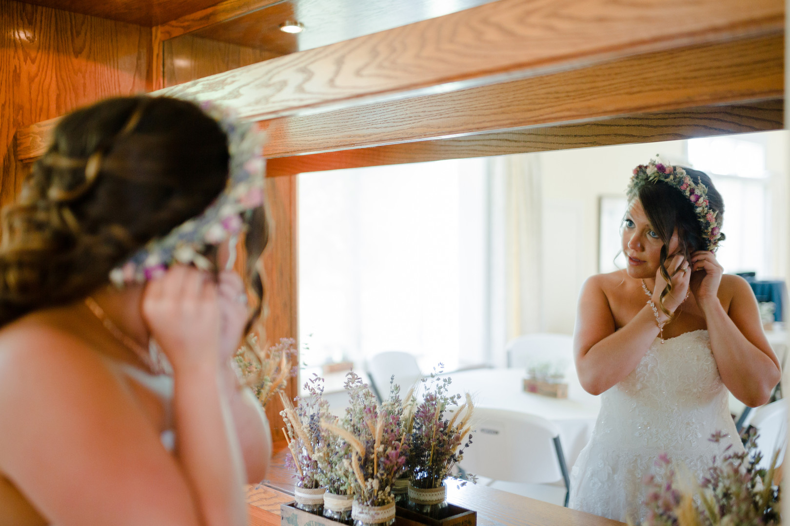 Bride putting on wedding jewelry: Rustic country wedding in Minooka, IL captured by Katie Brsan Photography. Visit CHItheeWED.com for more wedding inspiration!