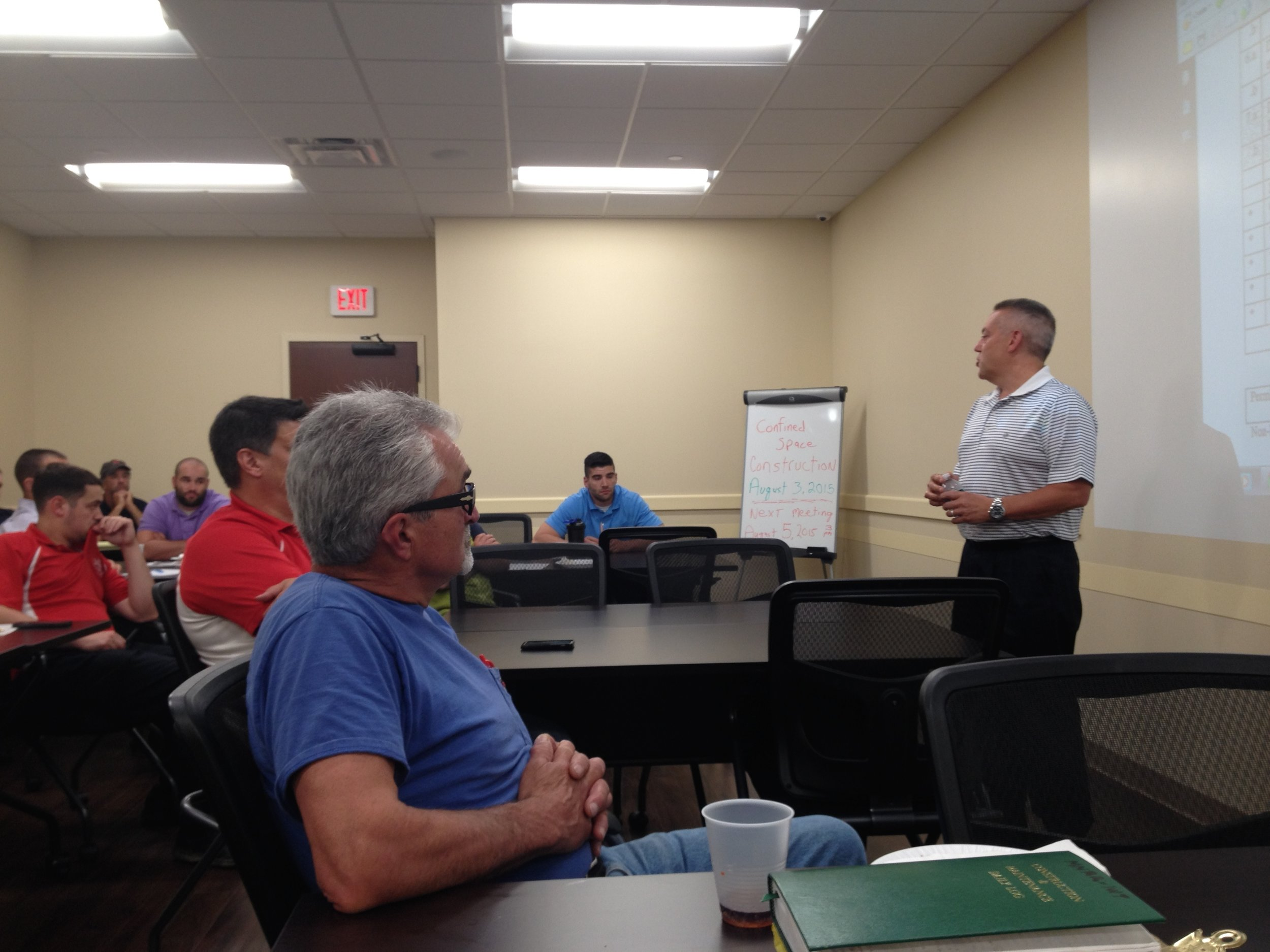 Anthony Rizzo Jr. discusses a new federal confined space regulation with construction managers at a safety meeting.