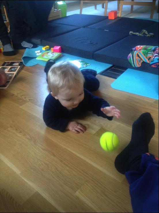 Asger, 10 mdr. gammel, er kravlet ned fra madrassen, hvor vi nu leger med en tennisbold
