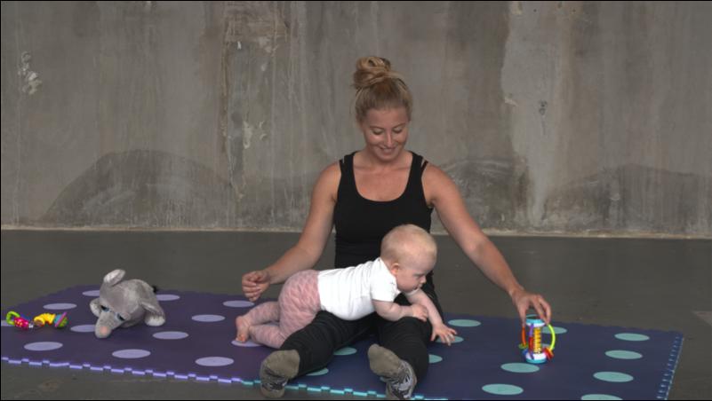 Pige på 8 mdr. kravler over mors ben efter et stykke legetøj  Øvelsen handler om at udfordre barnets generelle brug af kroppen med fokus på styrke og stabilitet.