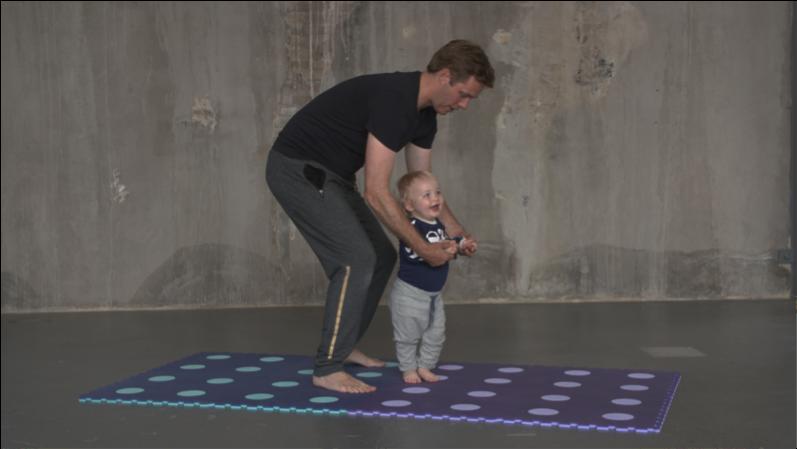 Conrad på 13 mdr. går baglæns mens jeg hjælper lidt.  Øvelsen træner barnets muskelkontrol.
