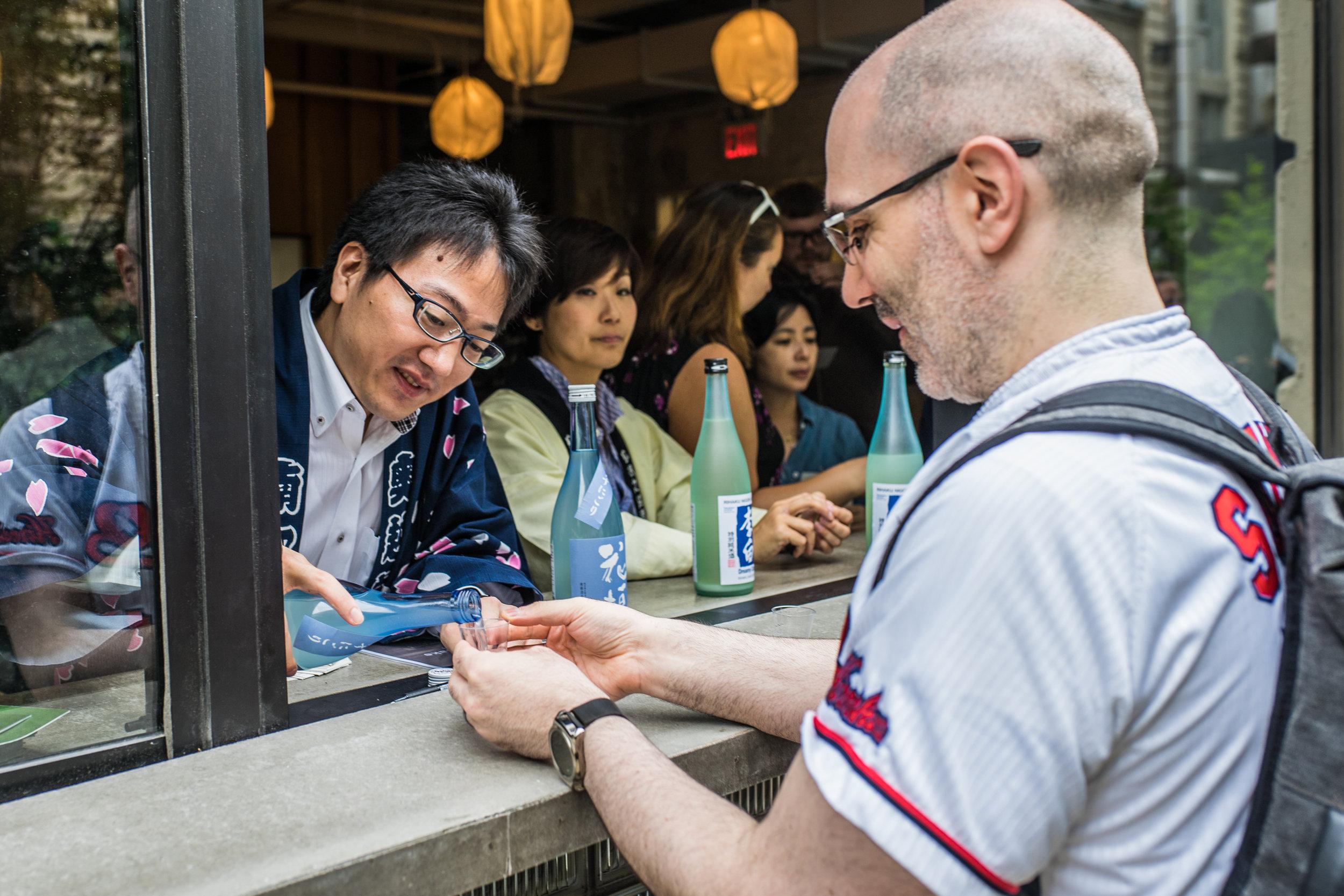 Nanbu Shuzo's Takuya Nambu pours John a taste of their excellent Hanagaki UsunigoriJunmai Daiginjo.