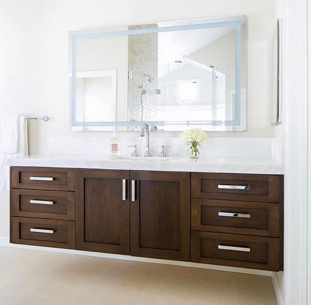 Who doesn't love a good floating vanity! The dark wood adds warmth and character to this bright and airy bathroom!  MTR Construction takes pride in creating a space their clients have always dreamed of having! • • • #mtrconstruction #buildersofig #orangecountycontractor #homebuilders #dreamkitchen #mtrkitchen #statecollegedistributors #designbuild #dreamhome #sherwinwilliams #anchorsaweigh #customcabinets #newportbeach #huntingtonbeach #coronadelmar #newportcoast #lagunabeach #longbeach #qualityconstruction #proudcontractor #bathroomvanity #floatingvanity #vanity #bathroom #wood #warmth #design