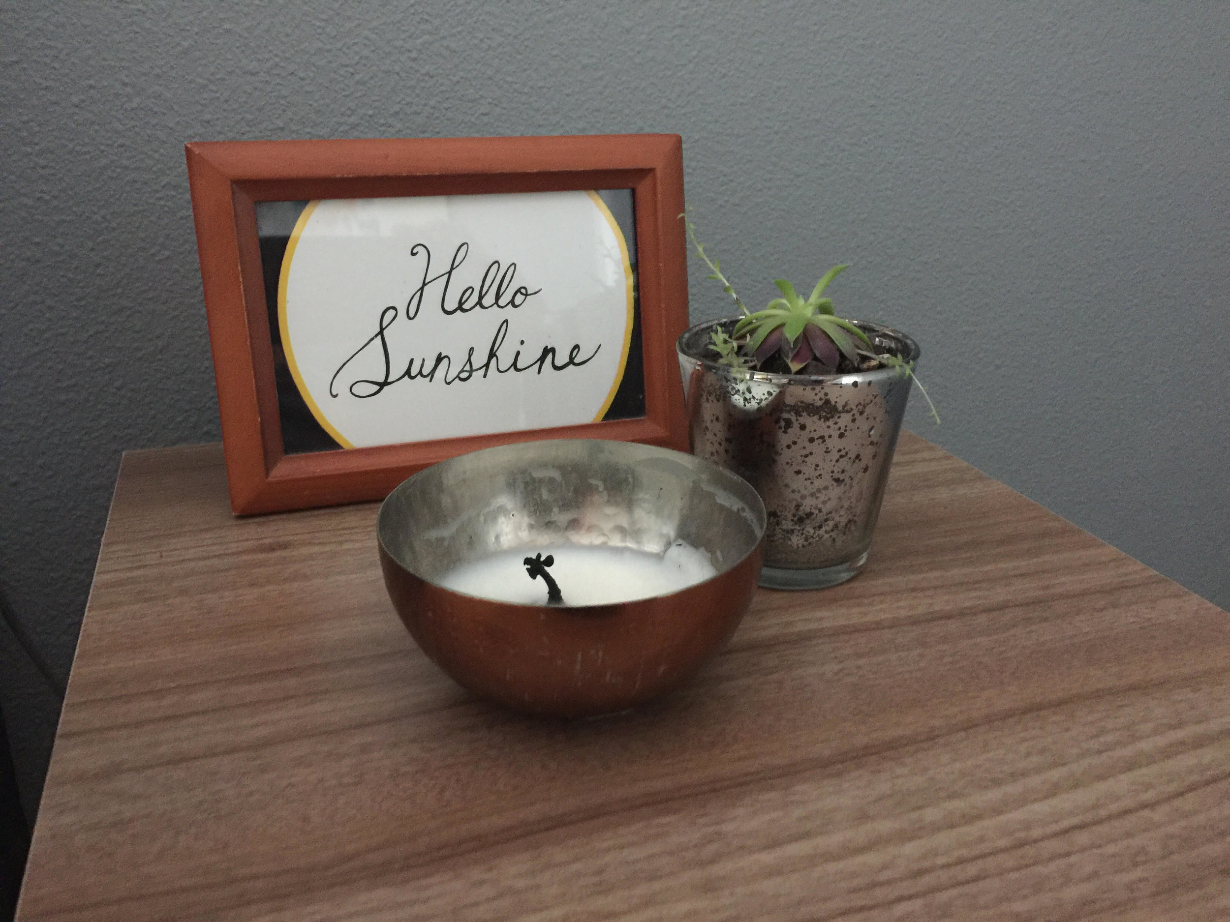 Three accessories. Three different items (artwork, plant, candle). Three heights.
