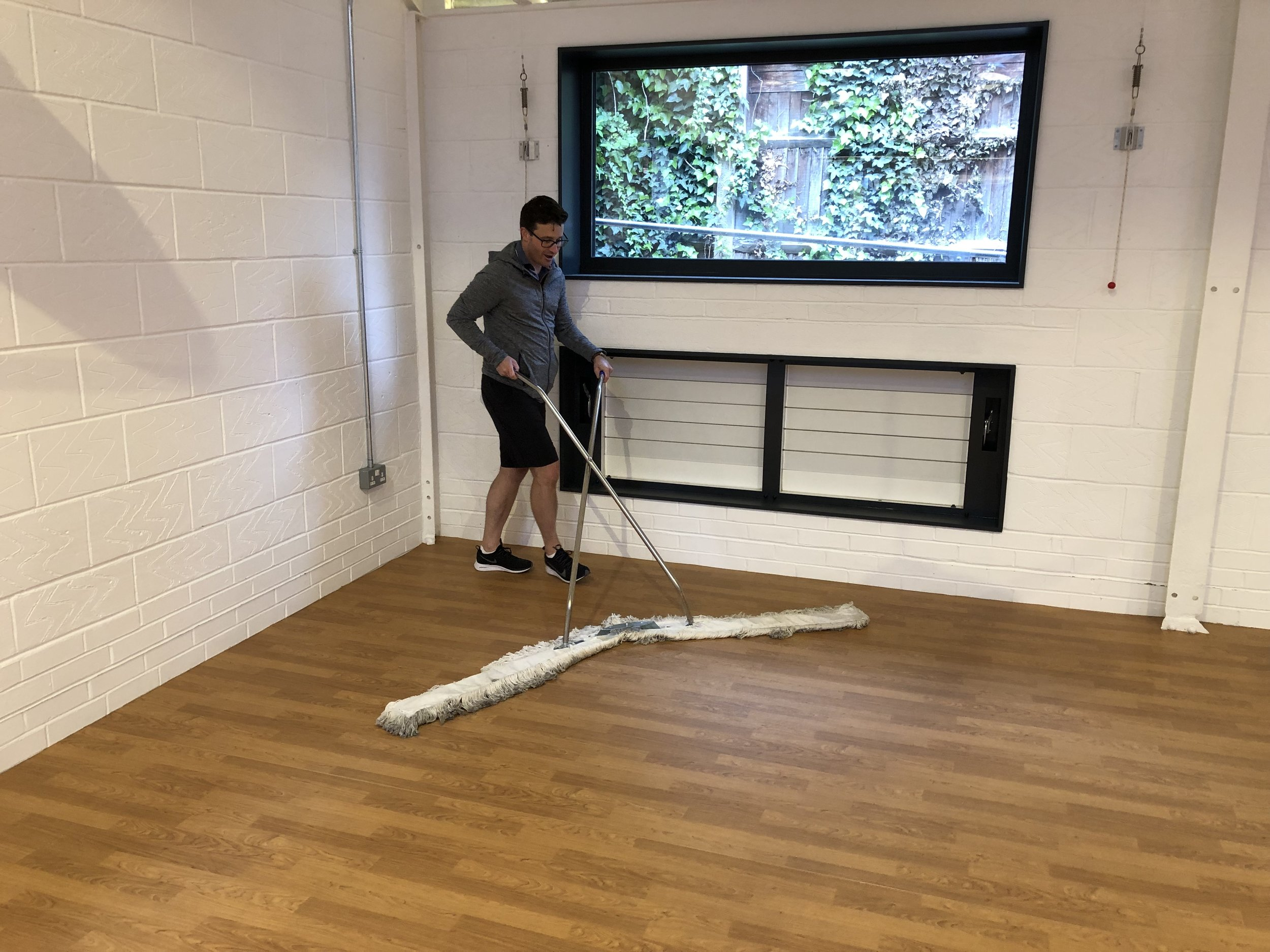 Jason Gray multi-tasking, enjoying polishing the new large gym floor