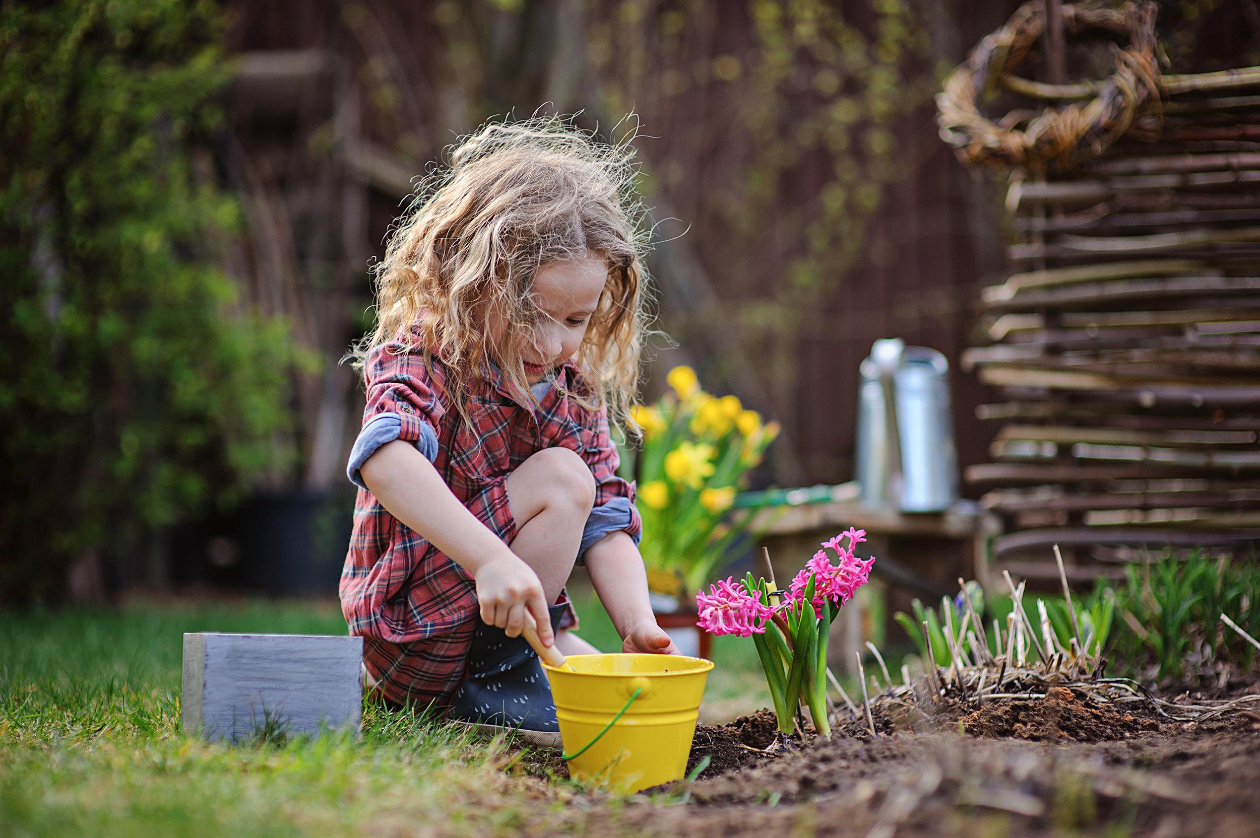 girl planting a flower in the garden