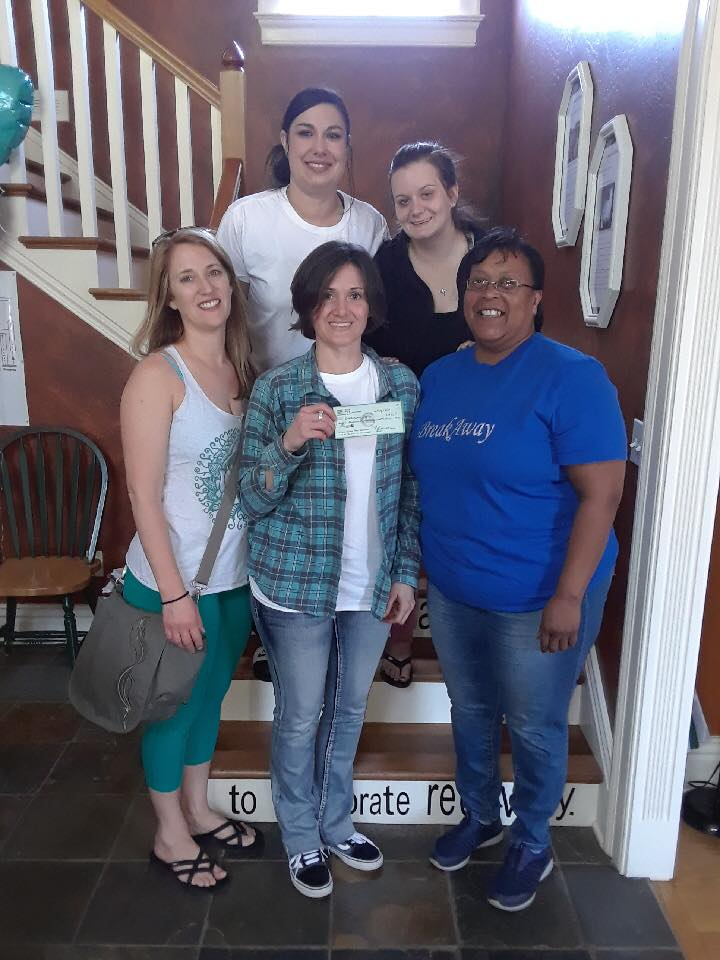 Inner Spring Yoga Owner/Director, Carrie Klaus, presenting The BreakAway Recovery home with a donation.