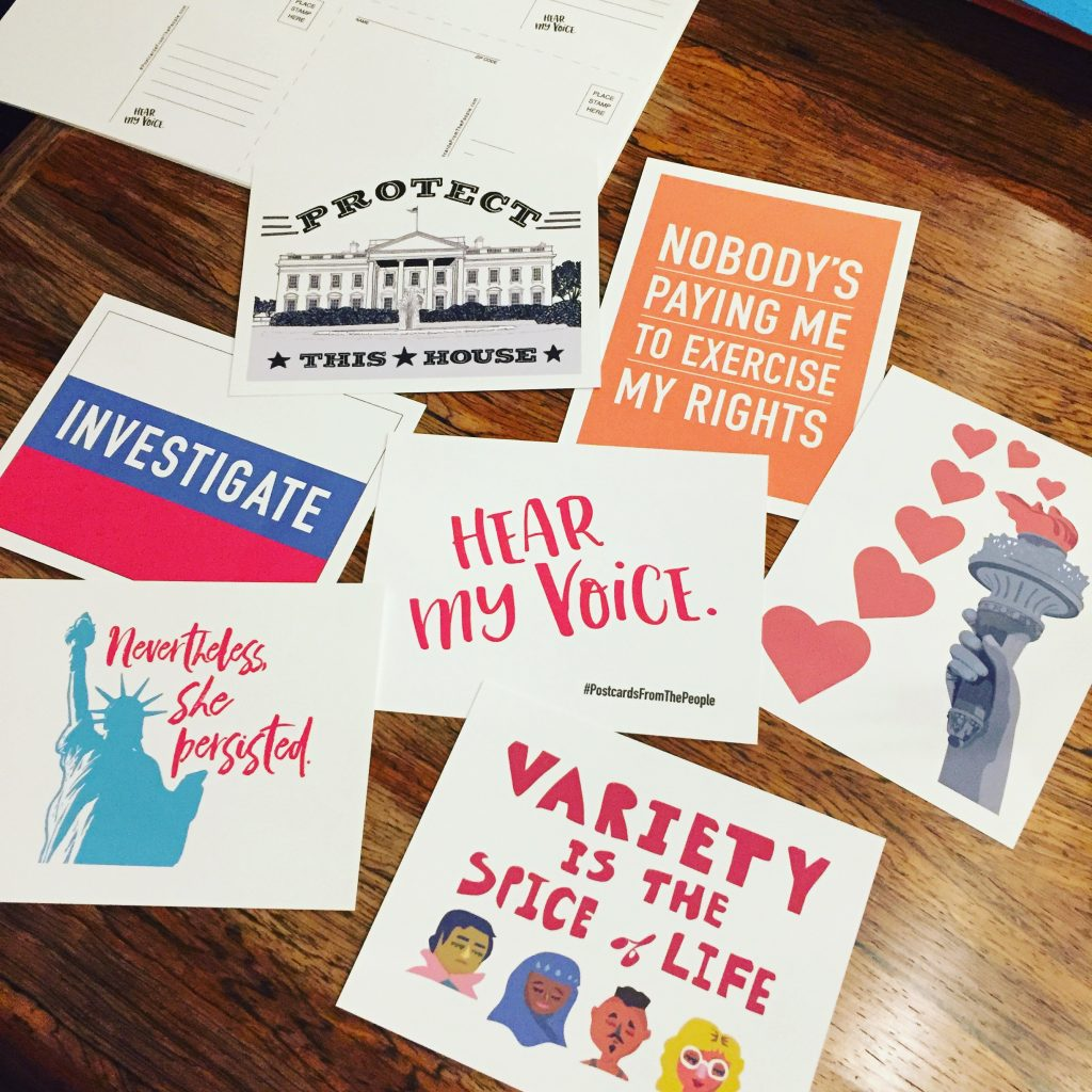 """Several Postcards From the People designs are displayed, including postcards that read, """"Investigate,"""" """"Nevertheless, she persisted,"""" """"Variety is the spice of life,"""" and """"Nobody's paying me to exercise my rights."""""""