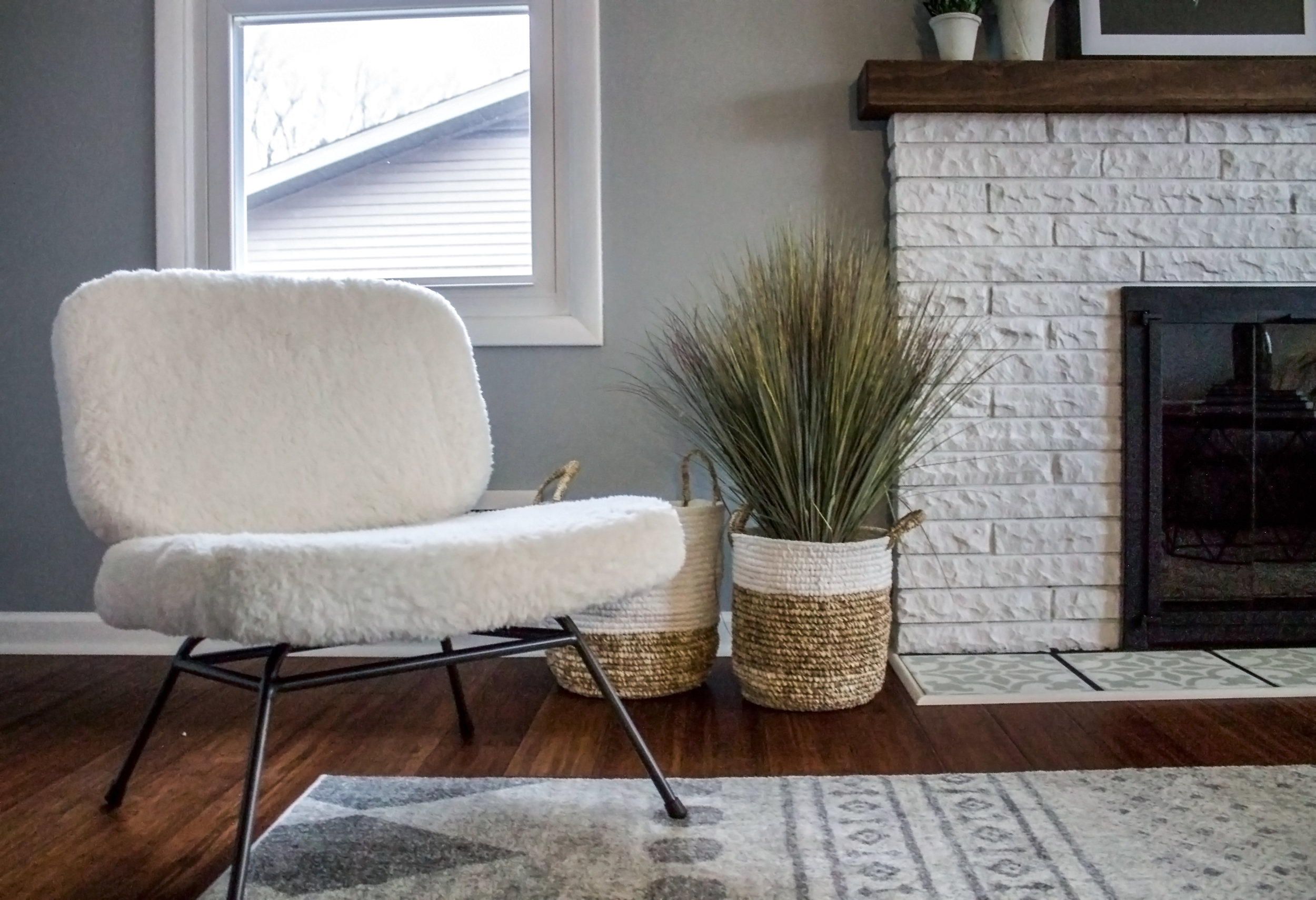 Caleb chair, white plush chair next to a white fireplace, trendy living room designed online, abbreviated design provides online interior design services in Grand Rapids Michigan,