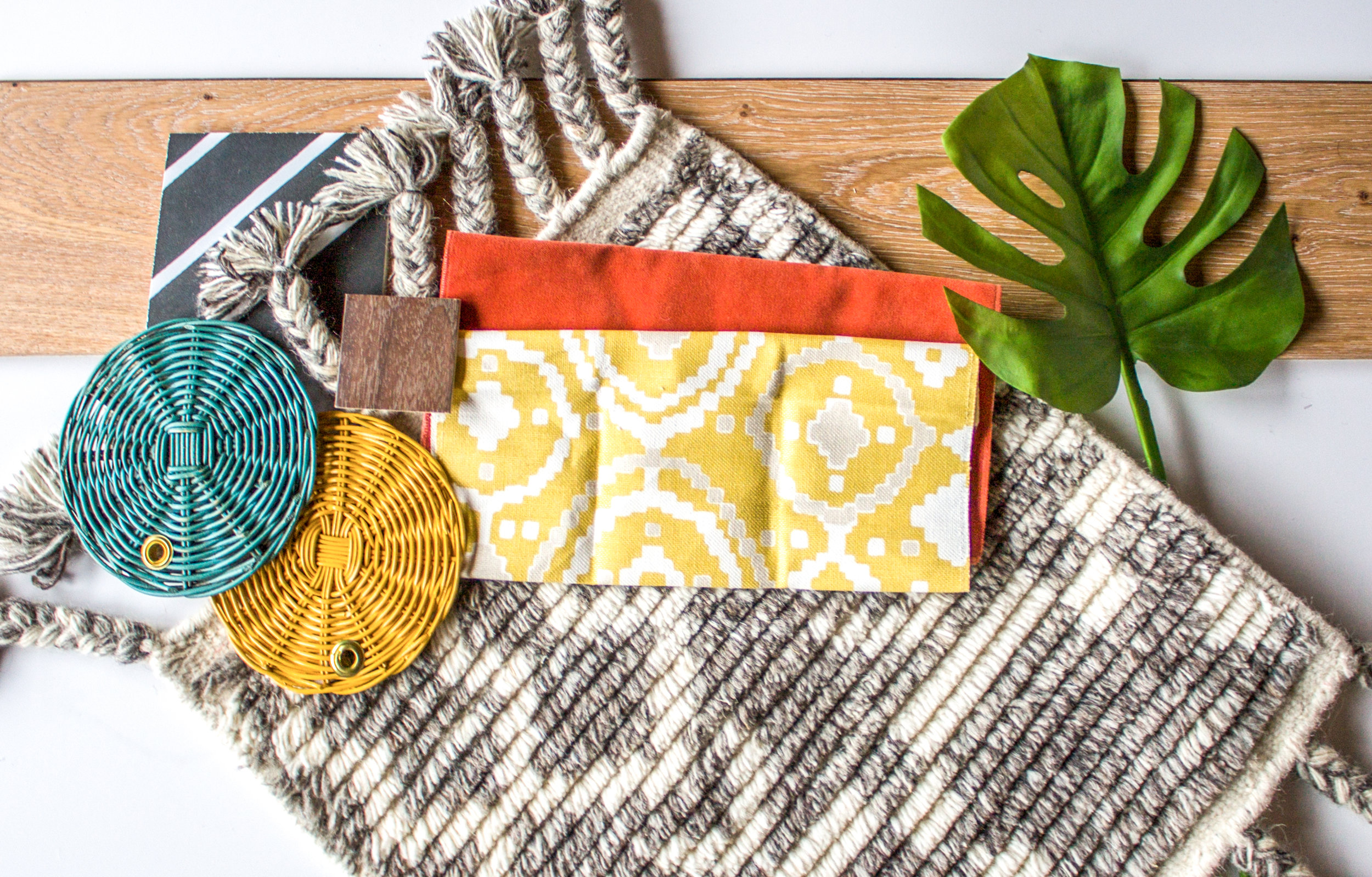 a collection of fabric samples for an interior design project, yellow fabric sample over an orange fabric, texture, plant leaf, abbreviated design provides online interior design services in Grand Rapids Michigan,