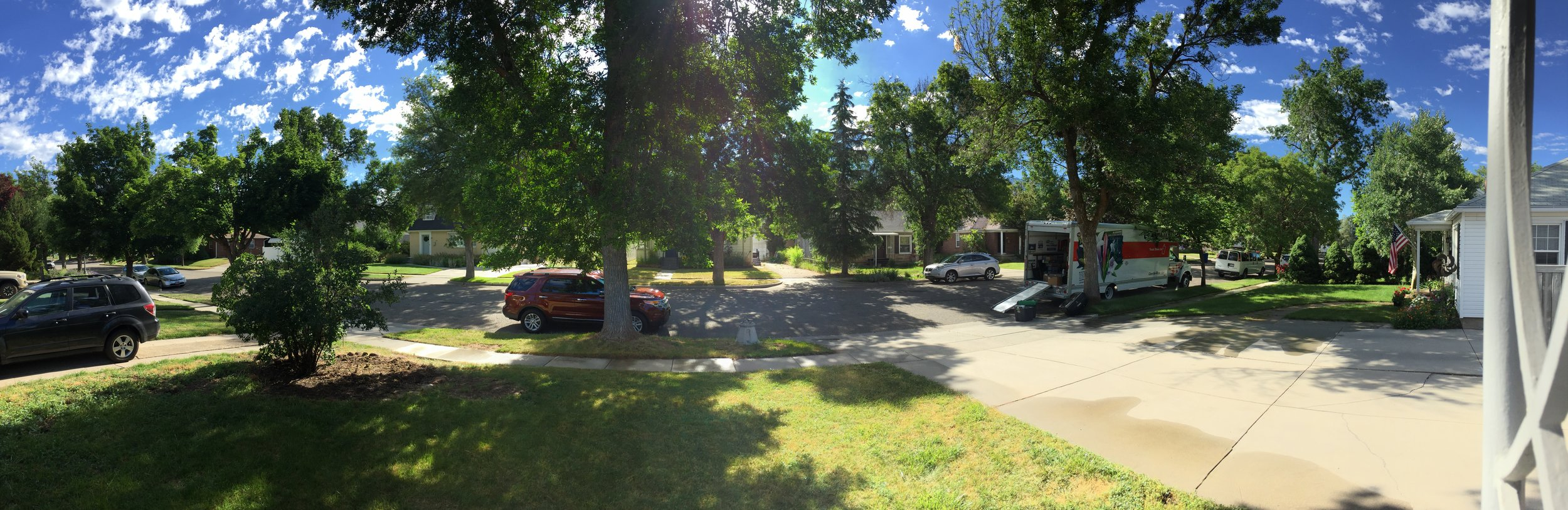 Beautiful new home! Blue sky, white puffy clouds, green tree-lined streets, and a lawn that needs a little work.