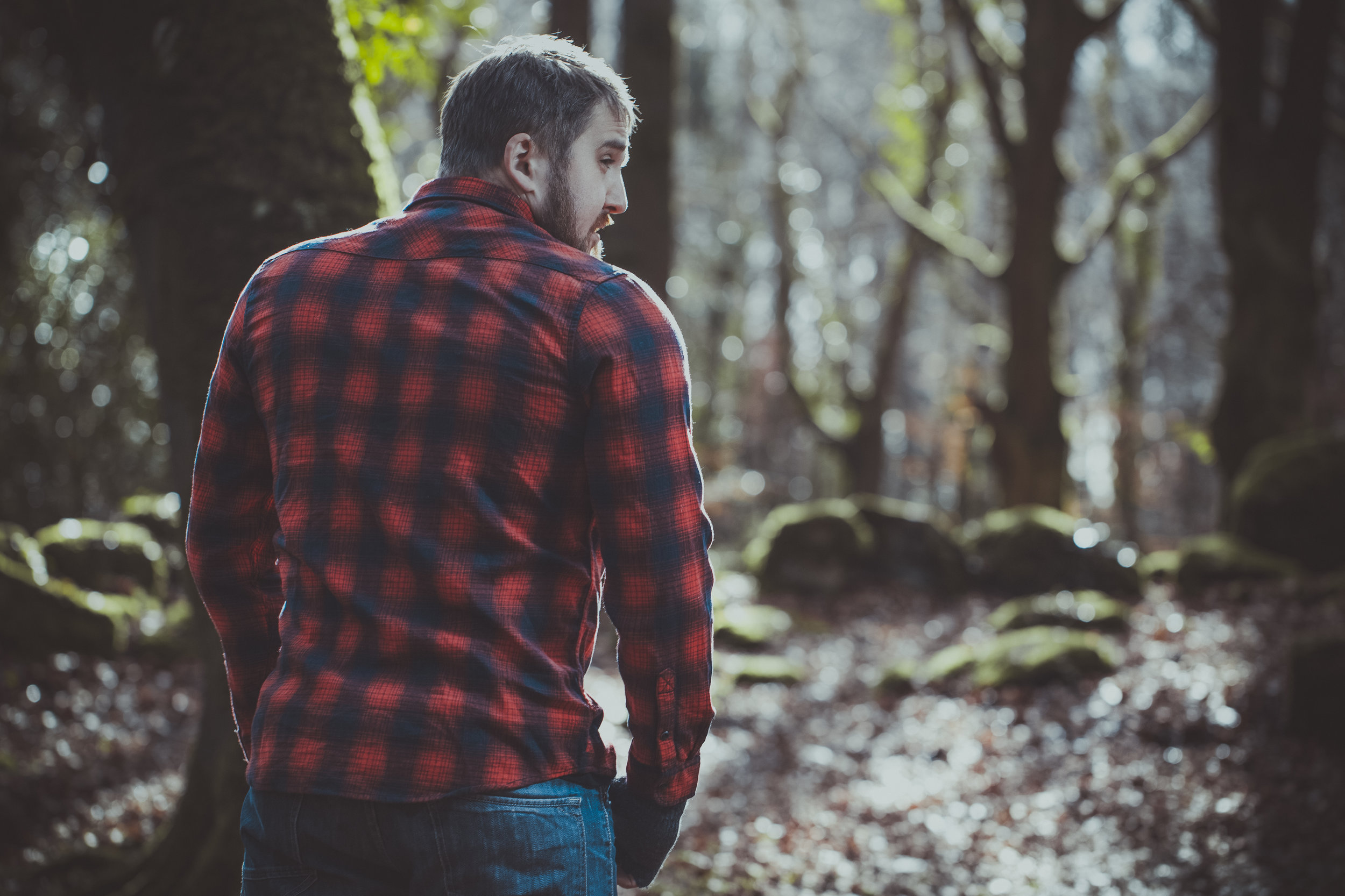 Man standing in forest in square shirt.