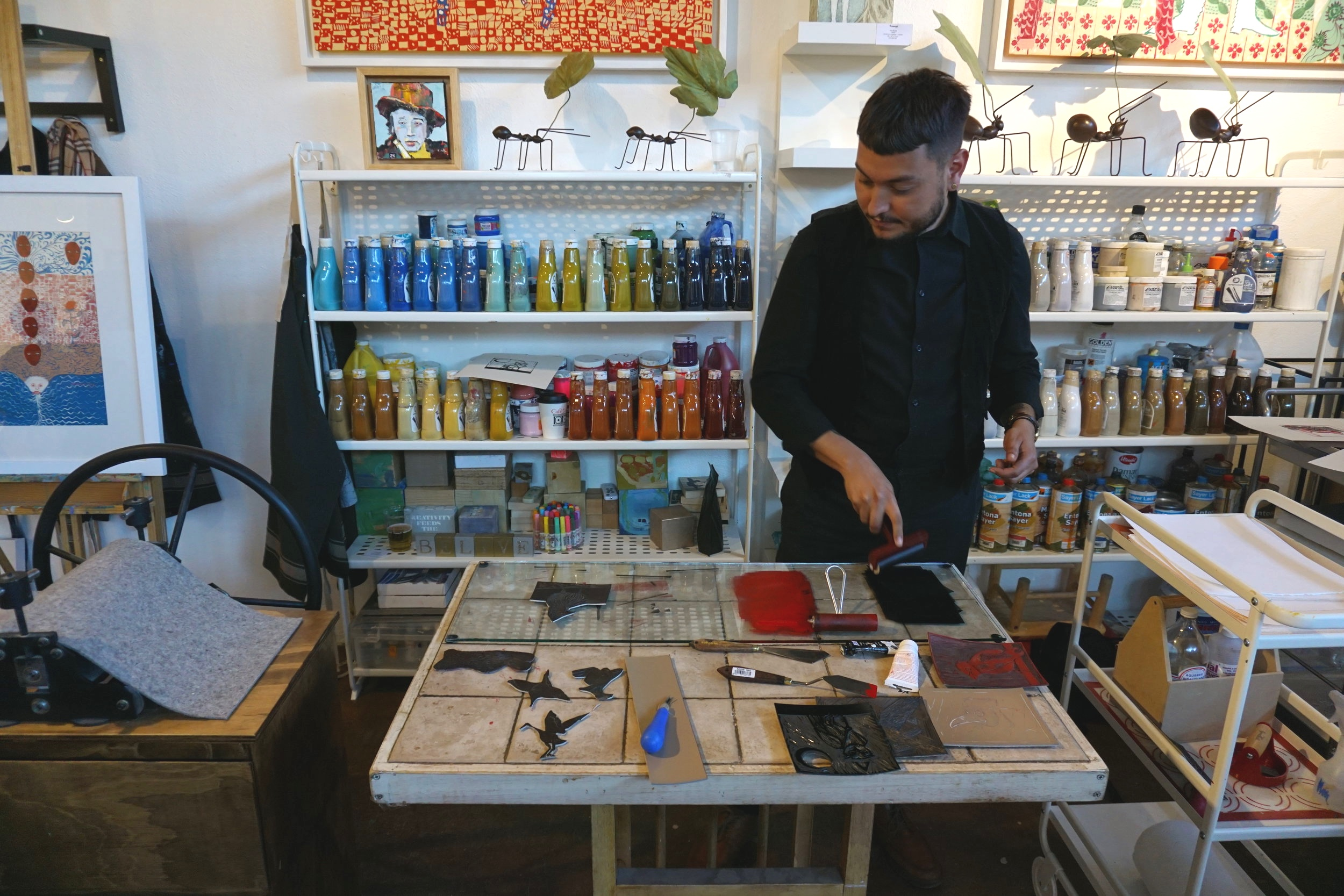 Artist Lorenzo Nuñez working on a linoleum design